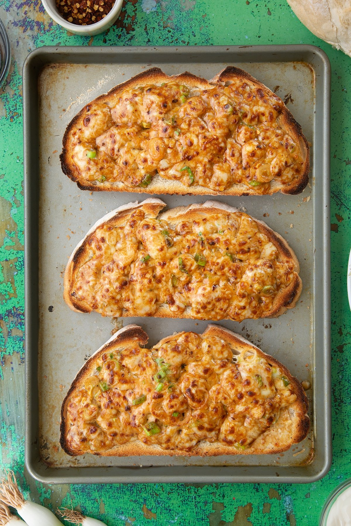 Three large slices of chilli cheese toast on a baking tray. Ingredients to make chilli cheese toast surround the tray.