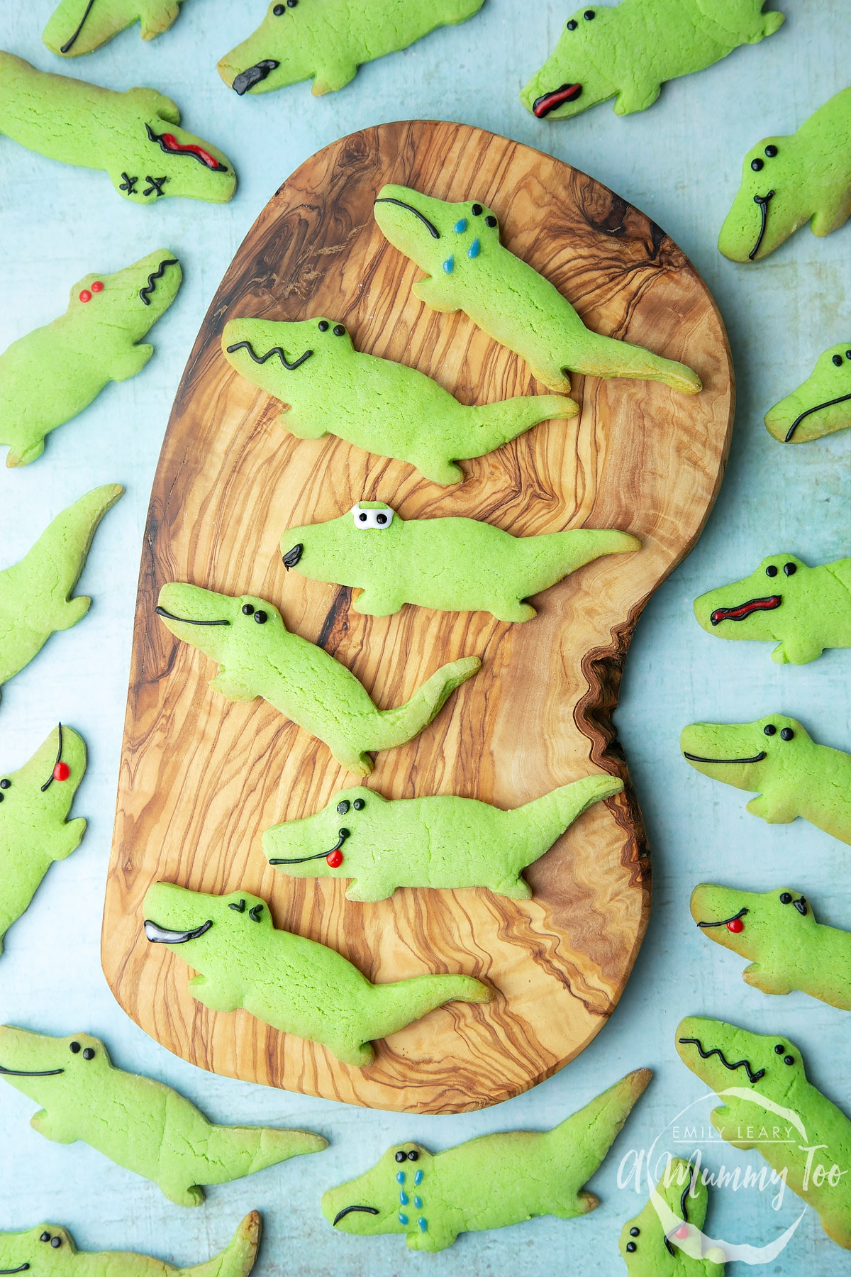 Overhead shot of green Crocodile cookies served on a wooden plate with a mummy too logo in the lower-right corner
