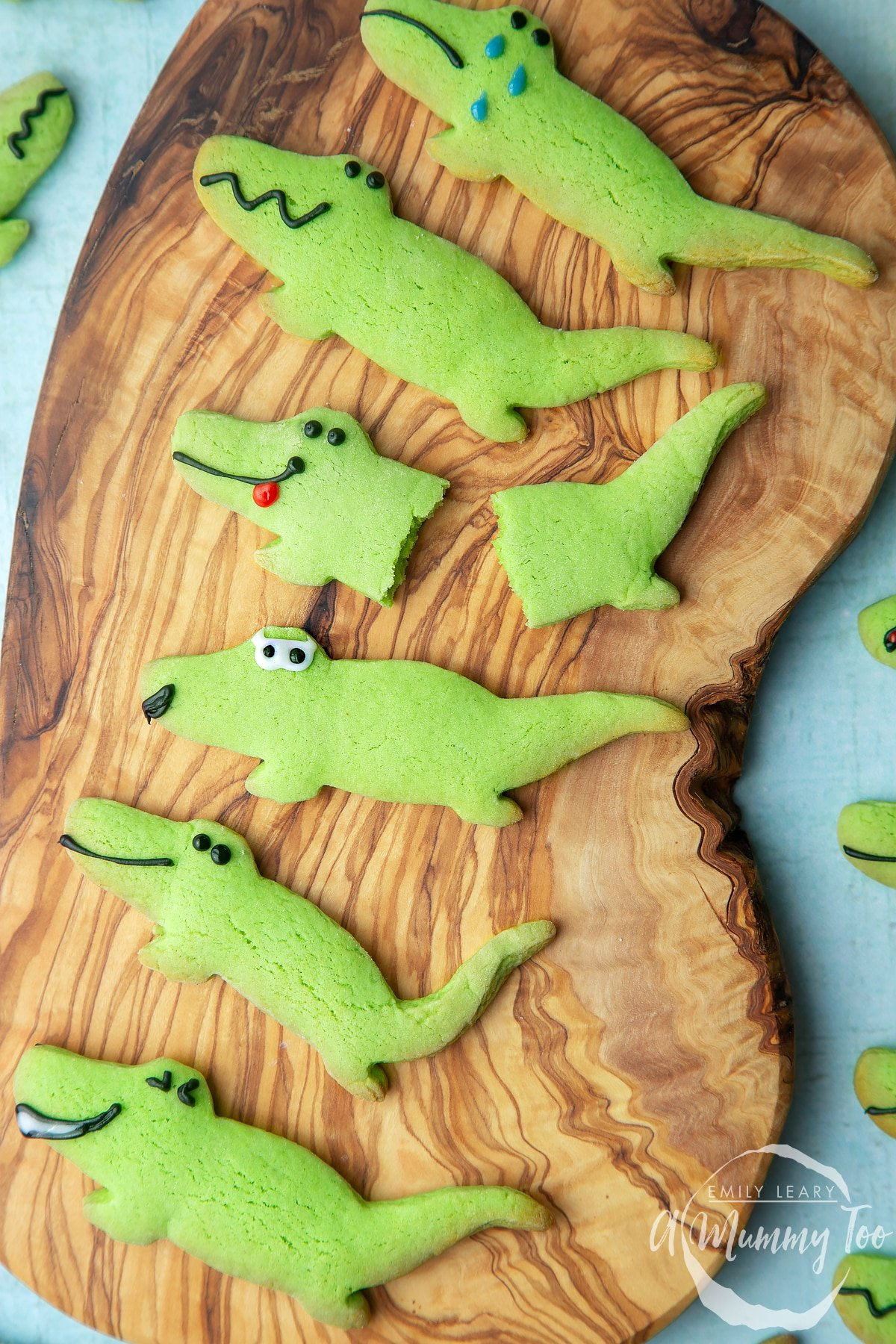Finished crocodile cookies on a wooden board.