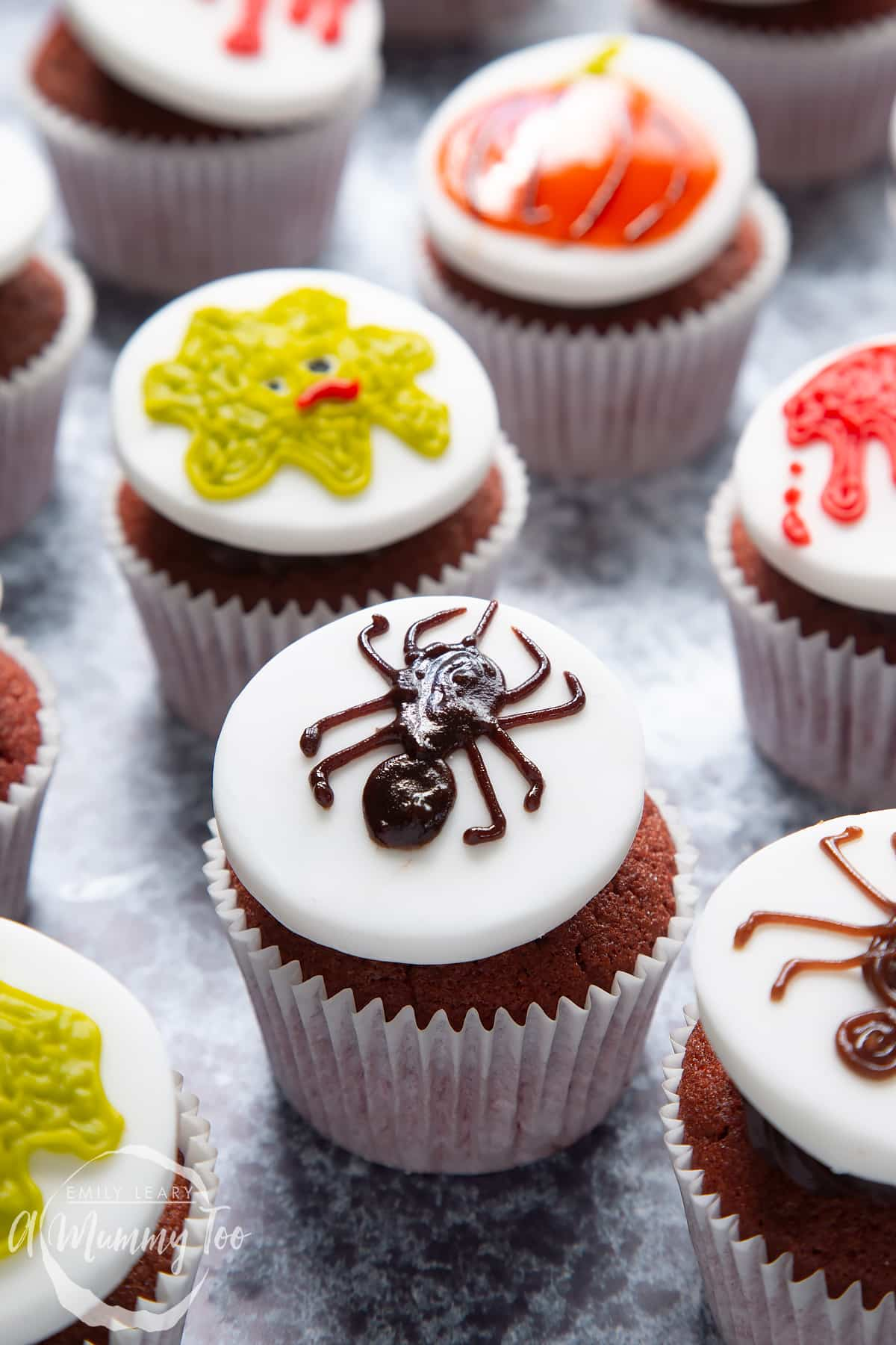 Dairy free Halloween cupcakes: red velvet cupcakes topped with chocolate frosting and white fondant discs decorated with icing pens. The cupcake in the foreground has a spider design.