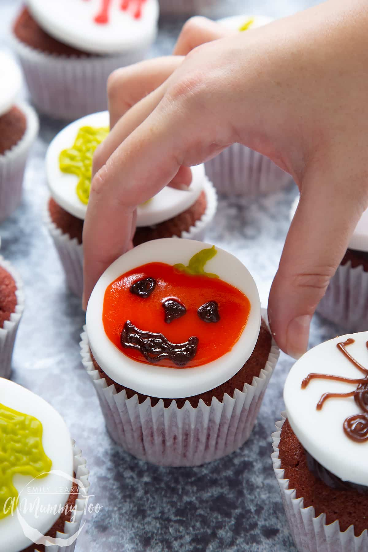 Dairy free Halloween cupcakes: red velvet cupcakes topped with chocolate frosting and white fondant discs decorated with icing pens. The cupcake in the foreground has a jack o'lantern design. A hand reaches to take it.