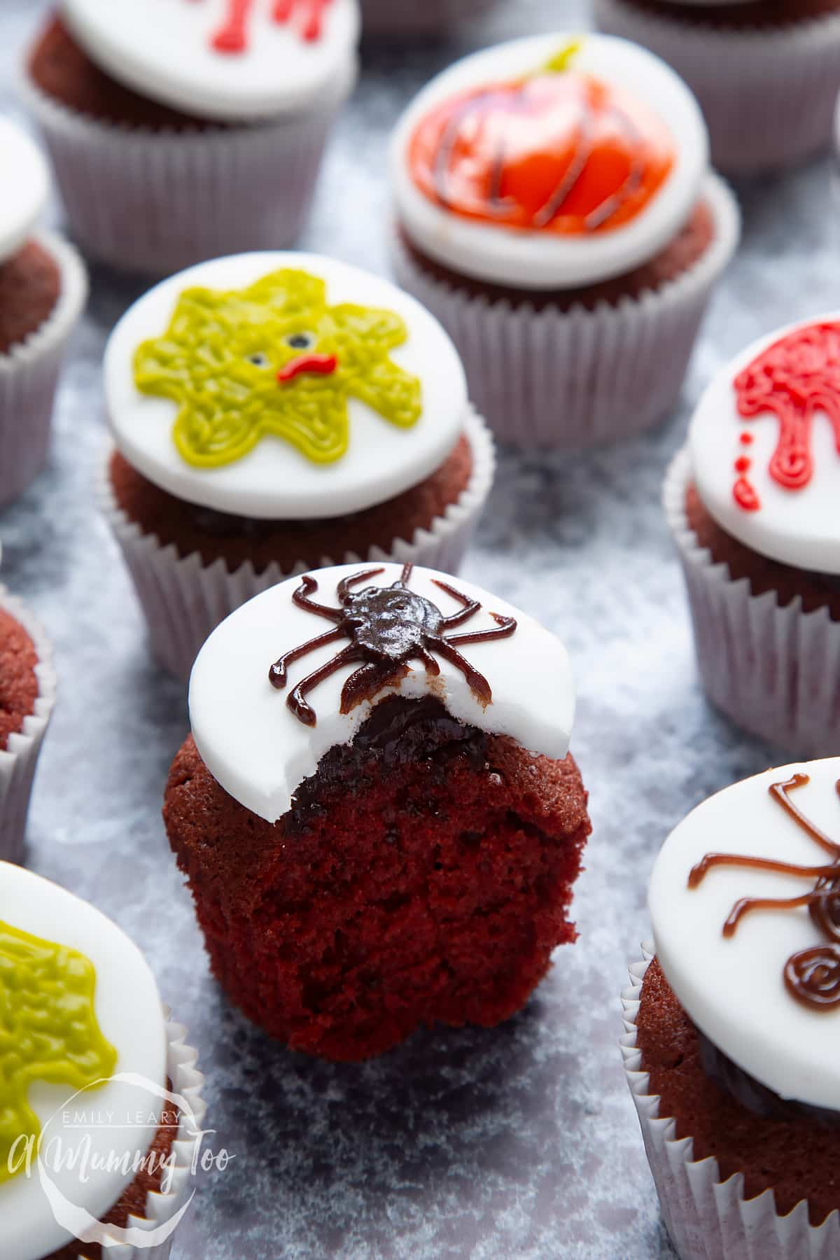 Dairy free Halloween cupcakes: red velvet cupcakes topped with chocolate frosting and white fondant discs decorated with icing pens. The cupcake in the foreground has a spider design with a bite out of it.