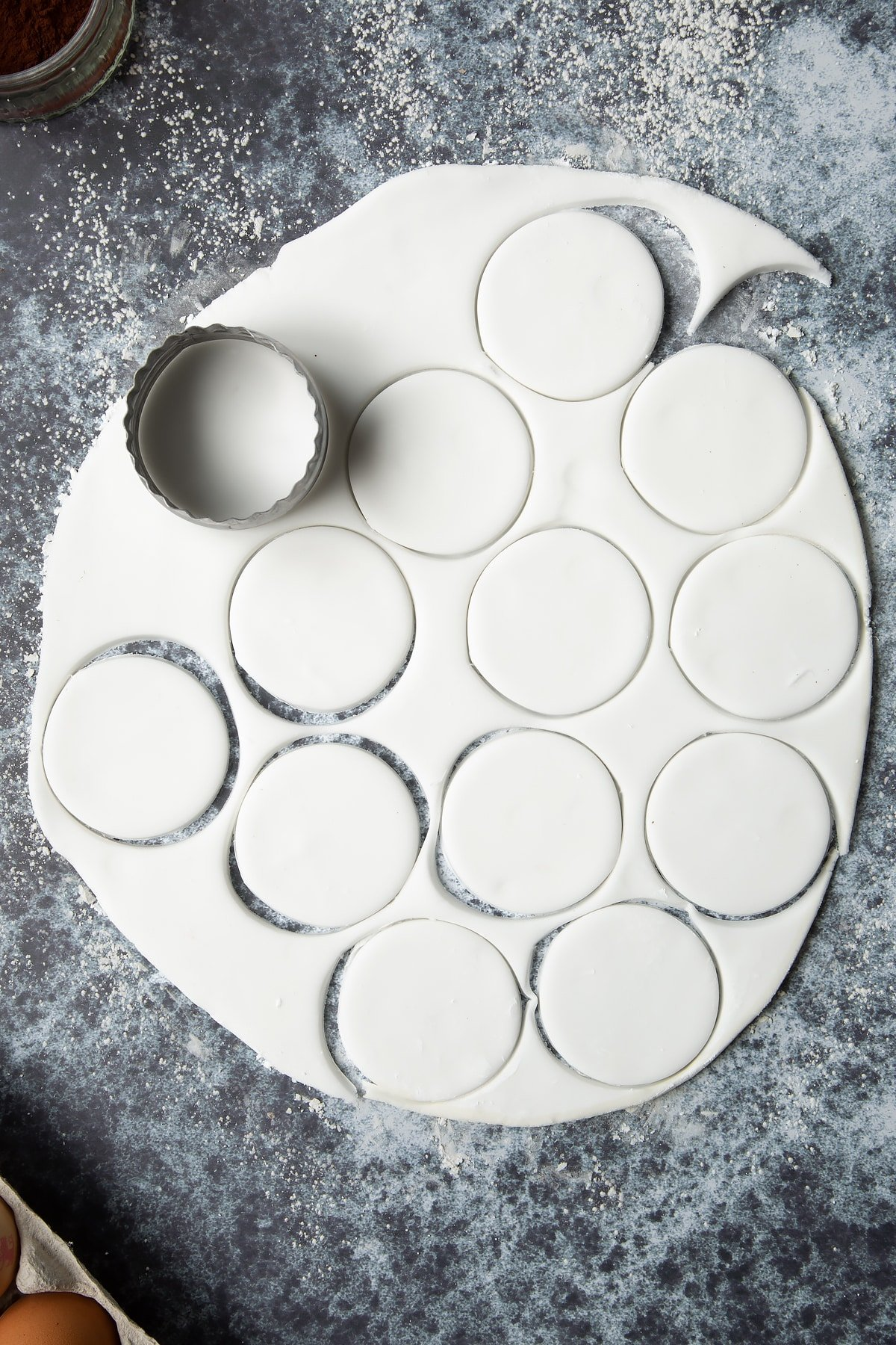 White sugar paste rolled out on a cornflour dusted surface. 12 discs have been cut from it.