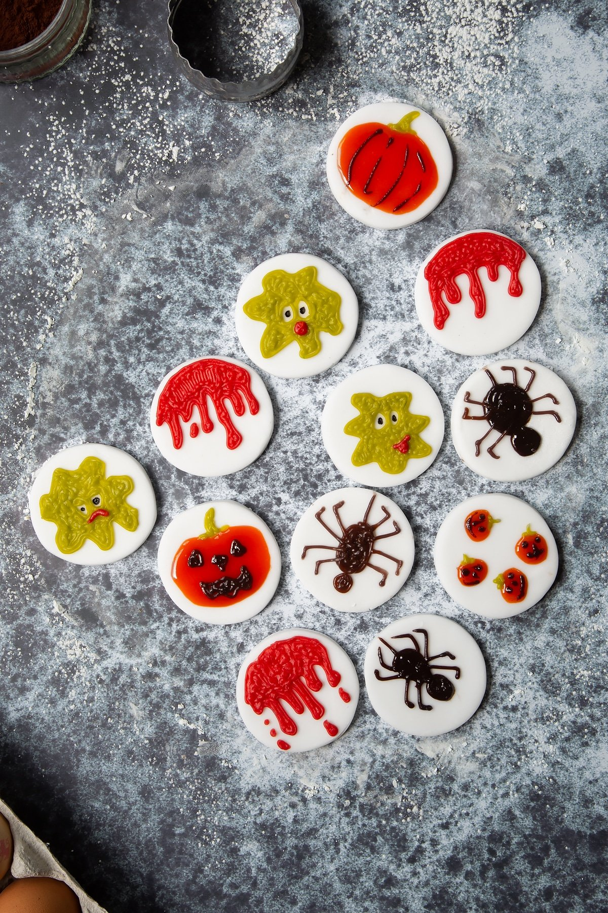 12 discs of white sugar paste out on a cornflour dusted surface, decorated with halloween symbols using icing pens.