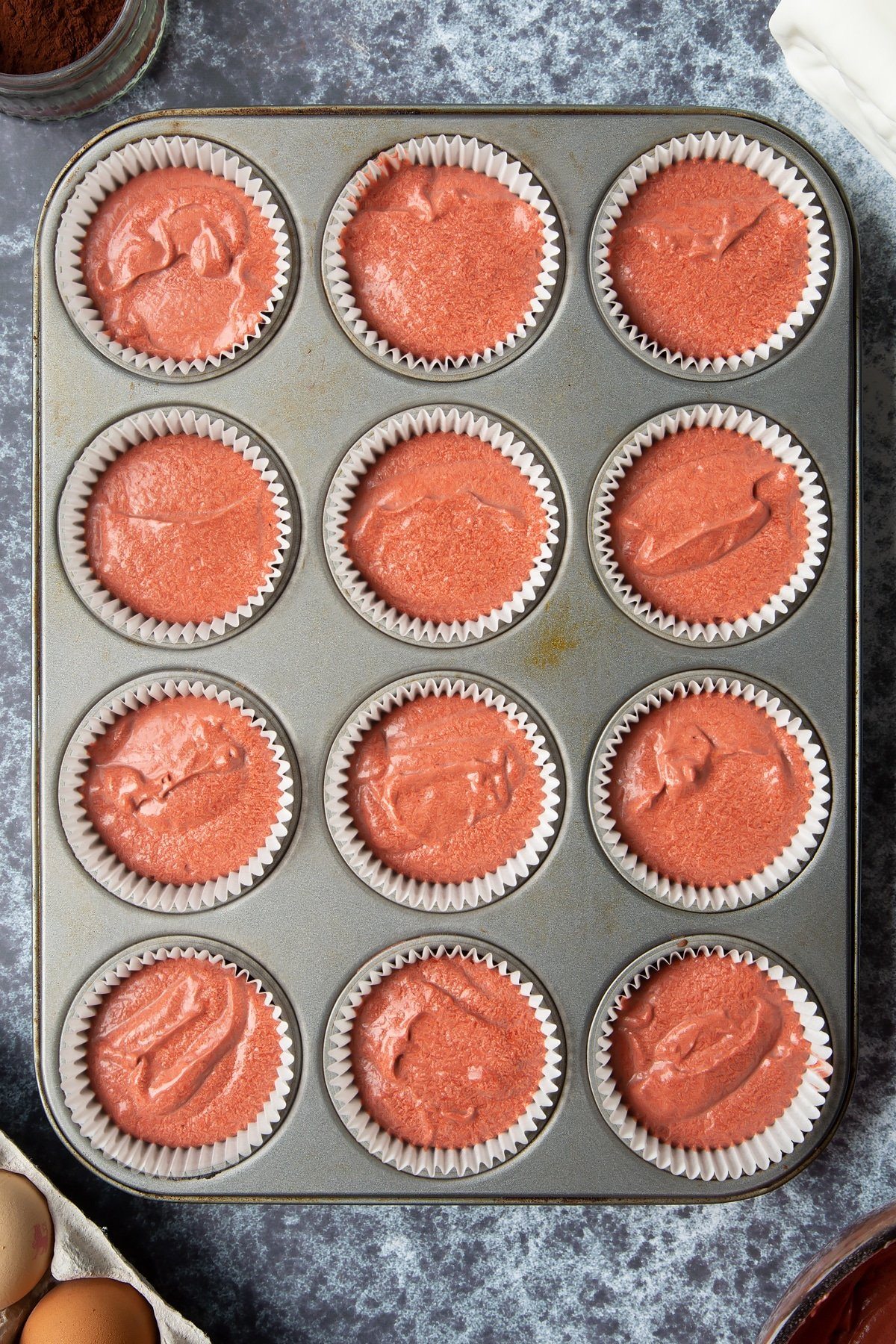 Lined 12-hole muffin tray filled with dairy free red velvet cupcake batter. Ingredients to make dairy free Halloween cupcakes surround the tray.