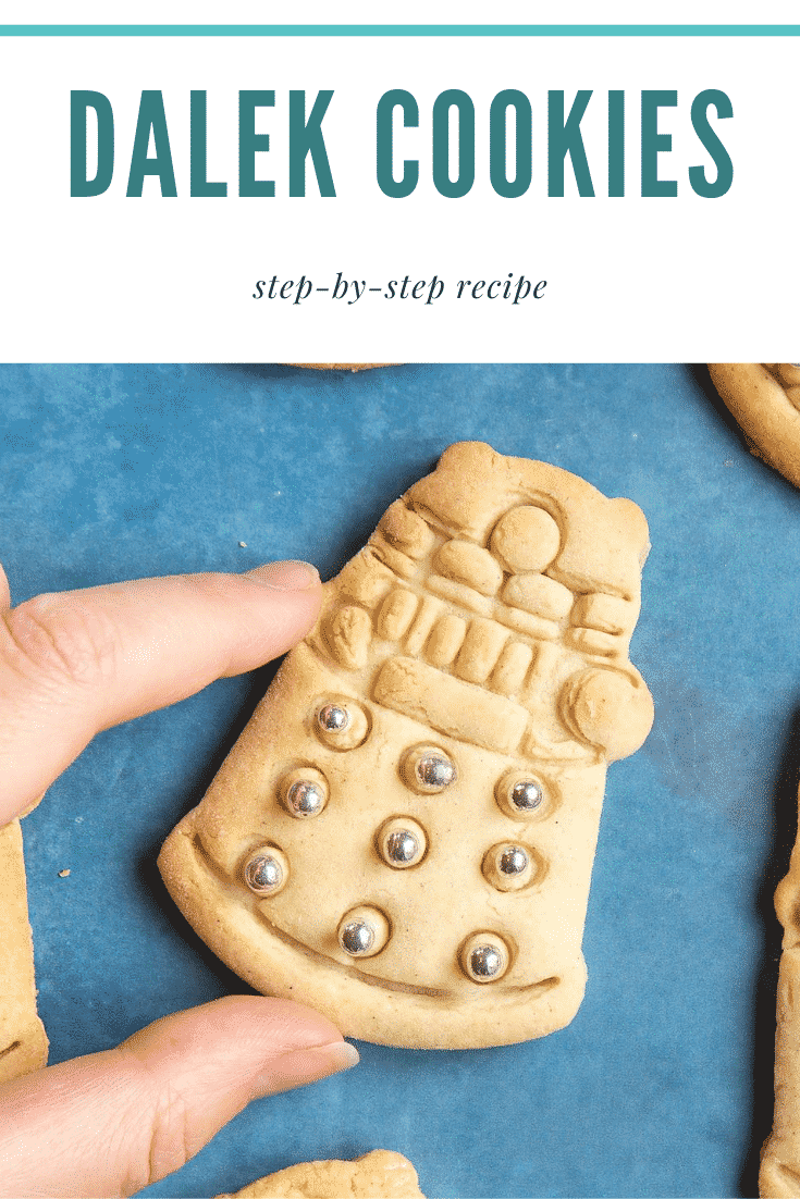 Hand holding a Dalek cookies decorated with silver candy balls. Caption reads: Dalek cookies step-by-step recipe