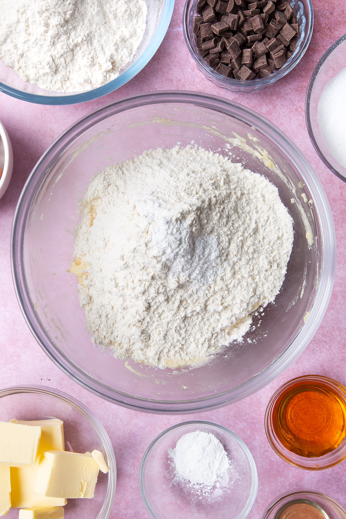 Overhead shot of butter, flour and baking powder in a large clear bowl