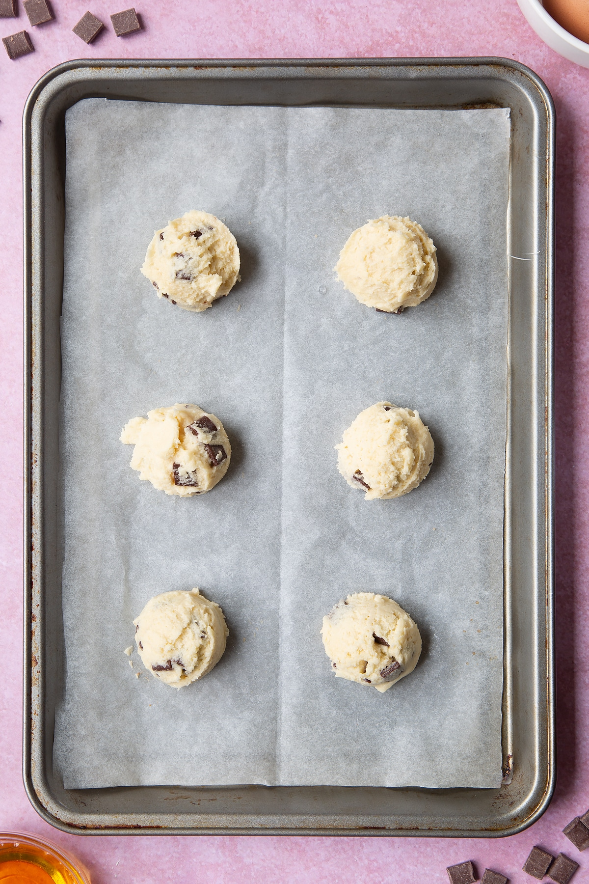 Overhead shot of chewy dark chocolate chip cookies dough on a baking tray