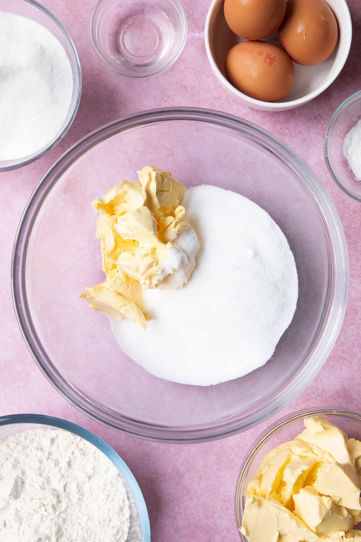 Overhead shot of margarine and sugar in a clear mixing bowl