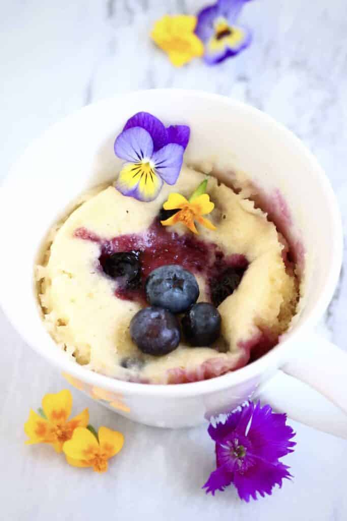 Vegan lemon blueberry mug cake, decorated with fresh blueberries and edible fllowers.