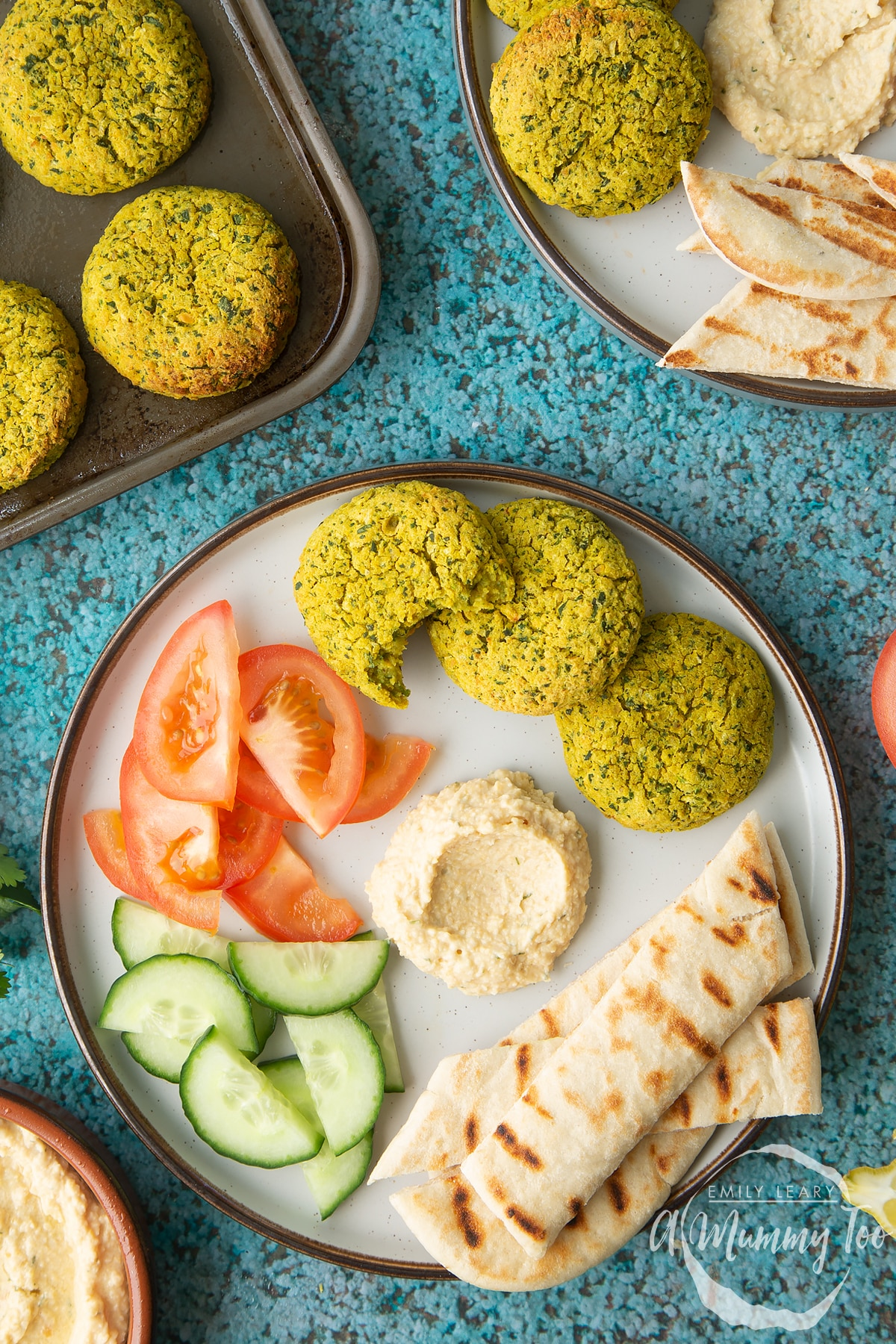 Gluten-free falafel on a plate with tomatoes, cucumber, hummus and  griddled flatbread. One of the falafel has a bite out of it.