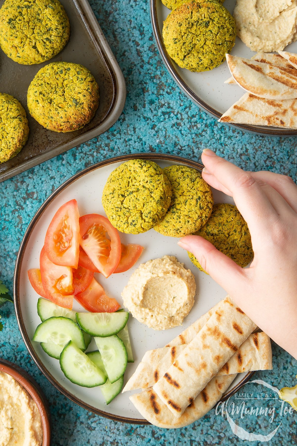 Gluten-free falafel on a plate with tomatoes, cucumber, hummus and  griddled flatbread. A hand reaches for one.
