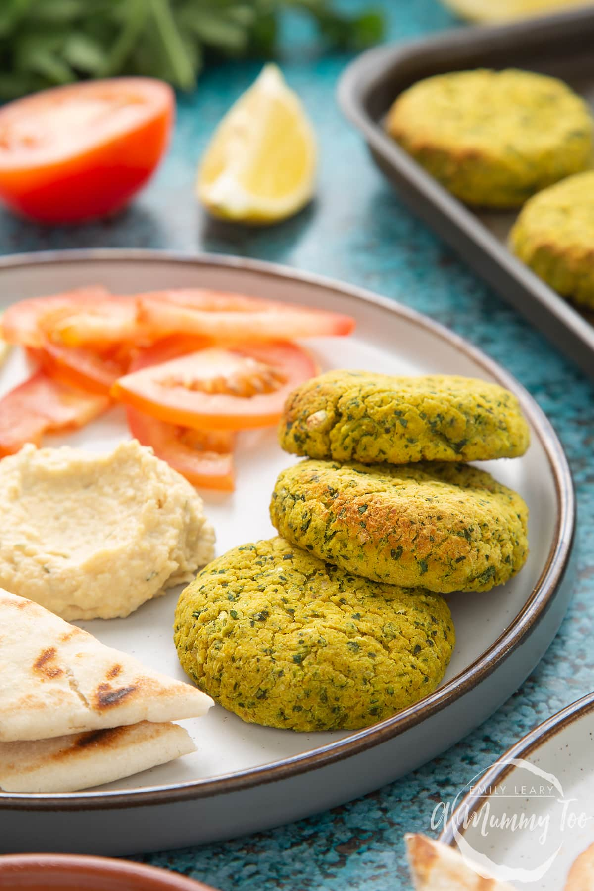Gluten-free falafel arranged on a plate with tomatoes, cucumber, hummus and  griddled flatbread.