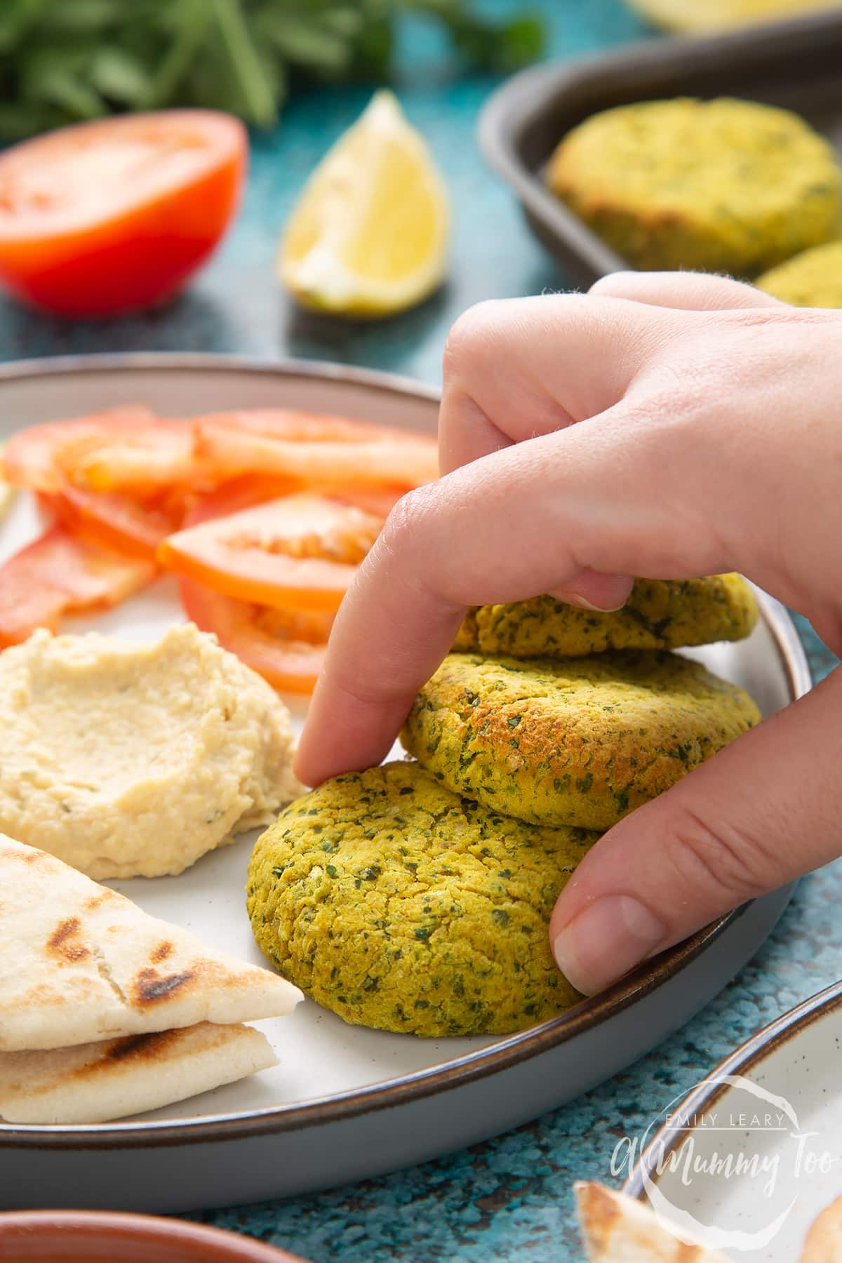 Gluten-free falafel arranged on a plate with tomatoes, cucumber, hummus and  griddled flatbread. A hand reaches to take one.