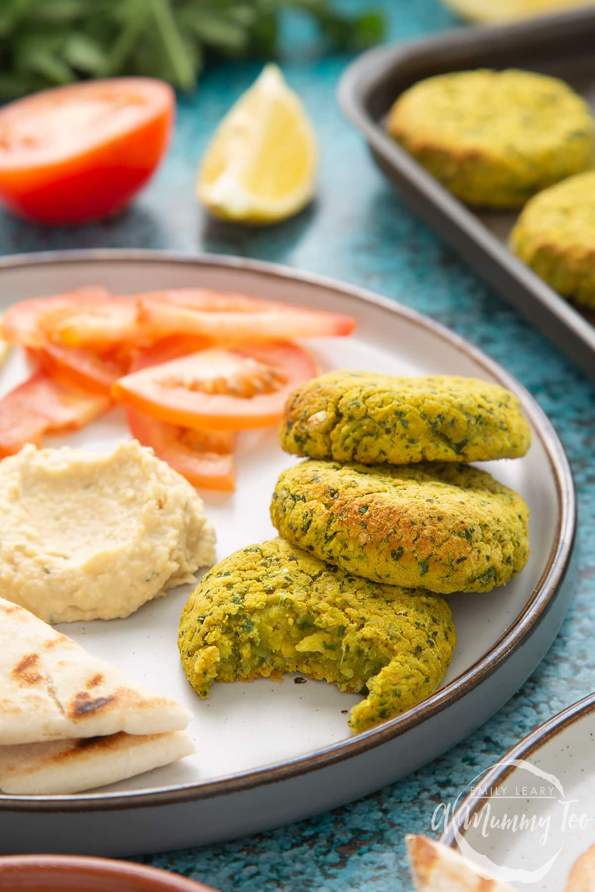 Gluten-free falafel arranged on a plate with tomatoes, cucumber, hummus and  griddled flatbread. One of the falafel has a bite out of it.