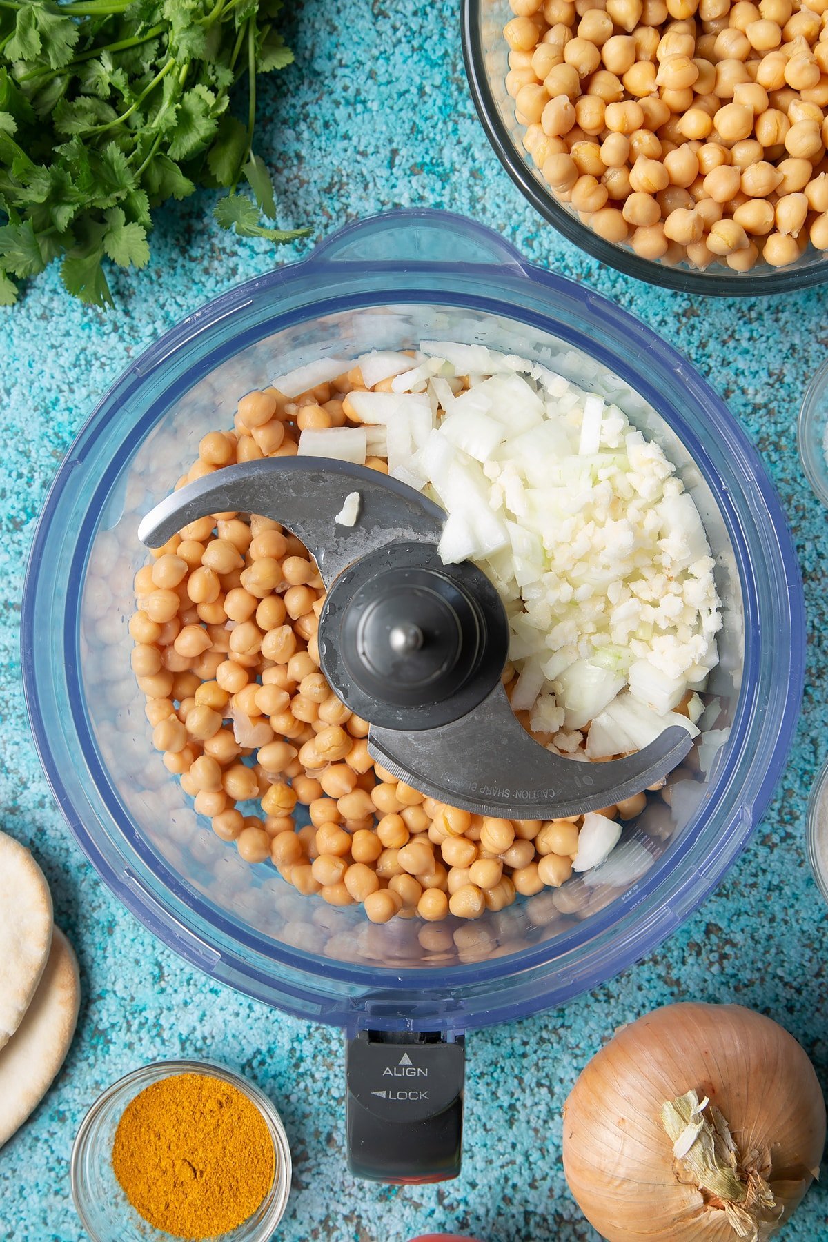 Chickpeas, onion and garlic in a food processor bowl. Ingredients to make gluten-free falafel surround the bowl.