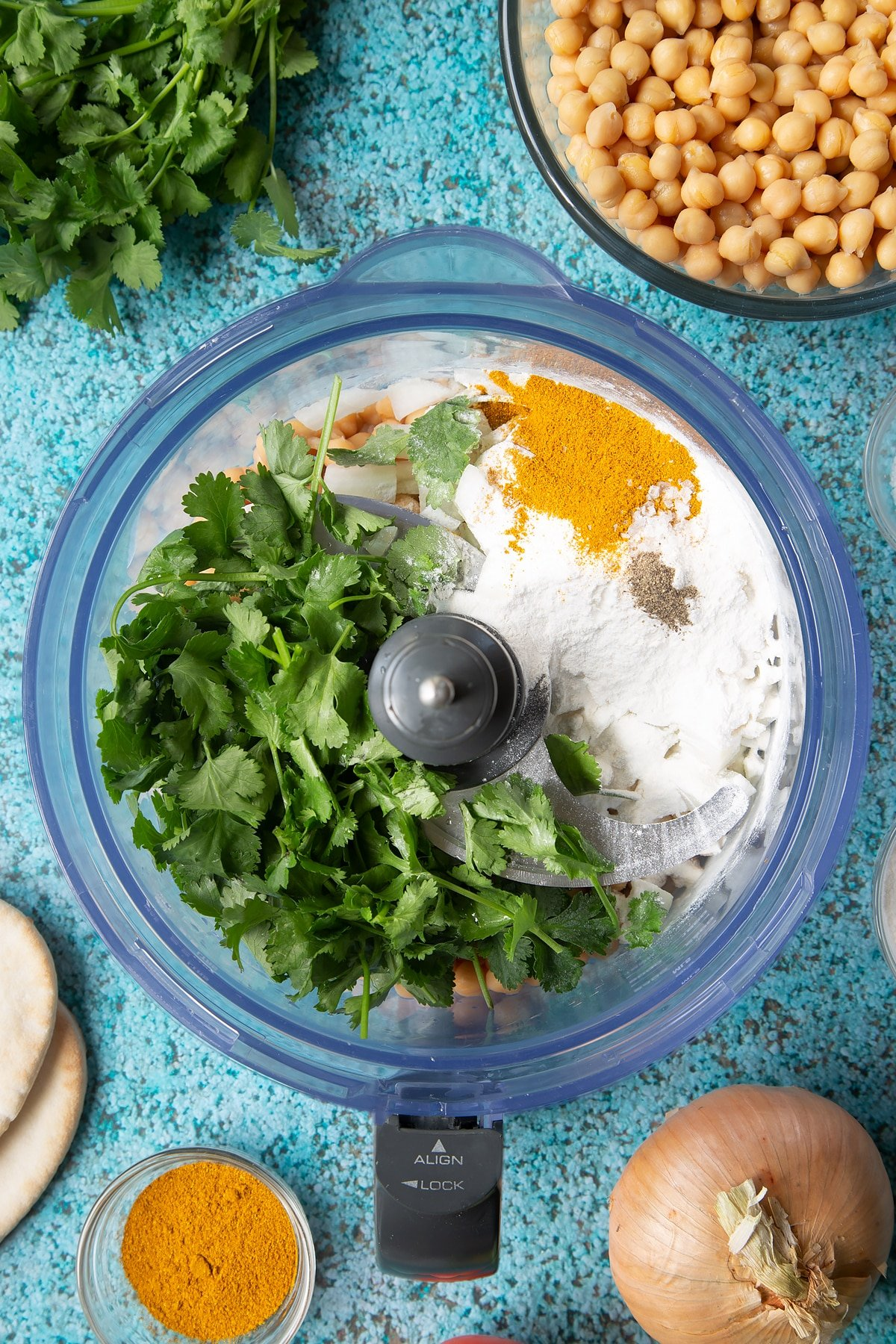 Chickpeas, onion, garlic, fresh coriander, gluten free flour, curry powder, salt and pepper in a food processor bowl. Ingredients to make gluten-free falafel surround the bowl.