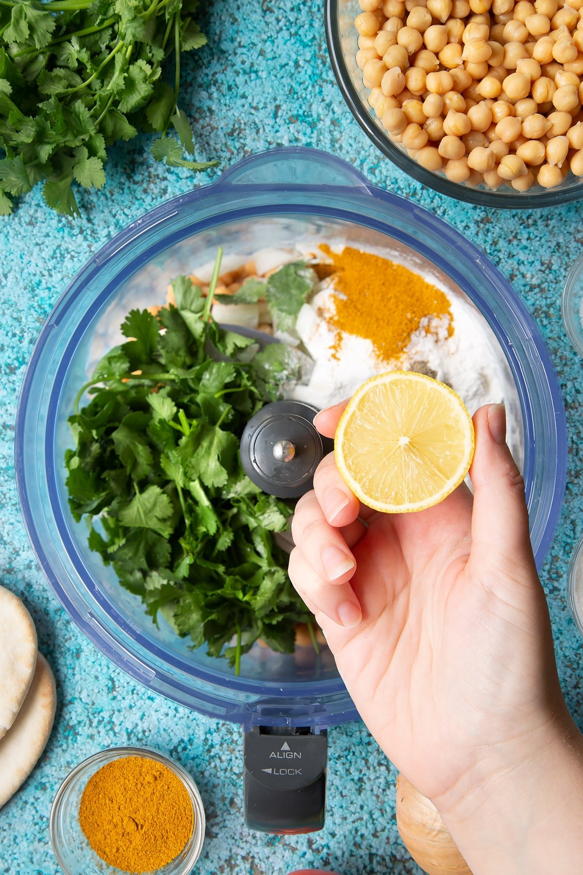 A hold holds a lemon half above chickpeas, onion, garlic, fresh coriander, gluten free flour, curry powder, salt and pepper in a food processor bowl. Ingredients to make gluten-free falafel surround the bowl.
