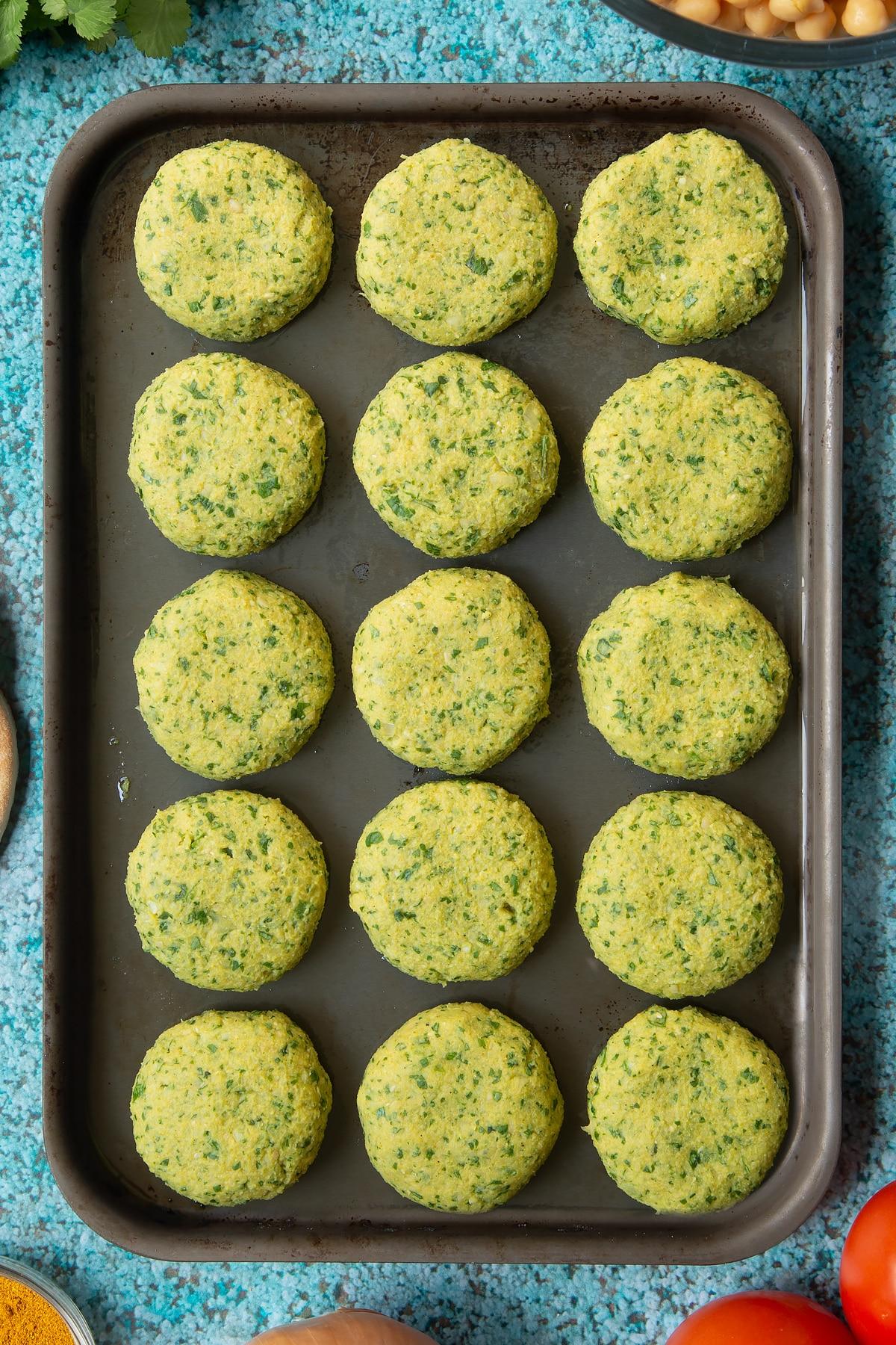 Raw gluten-free falafel on a baking tray.