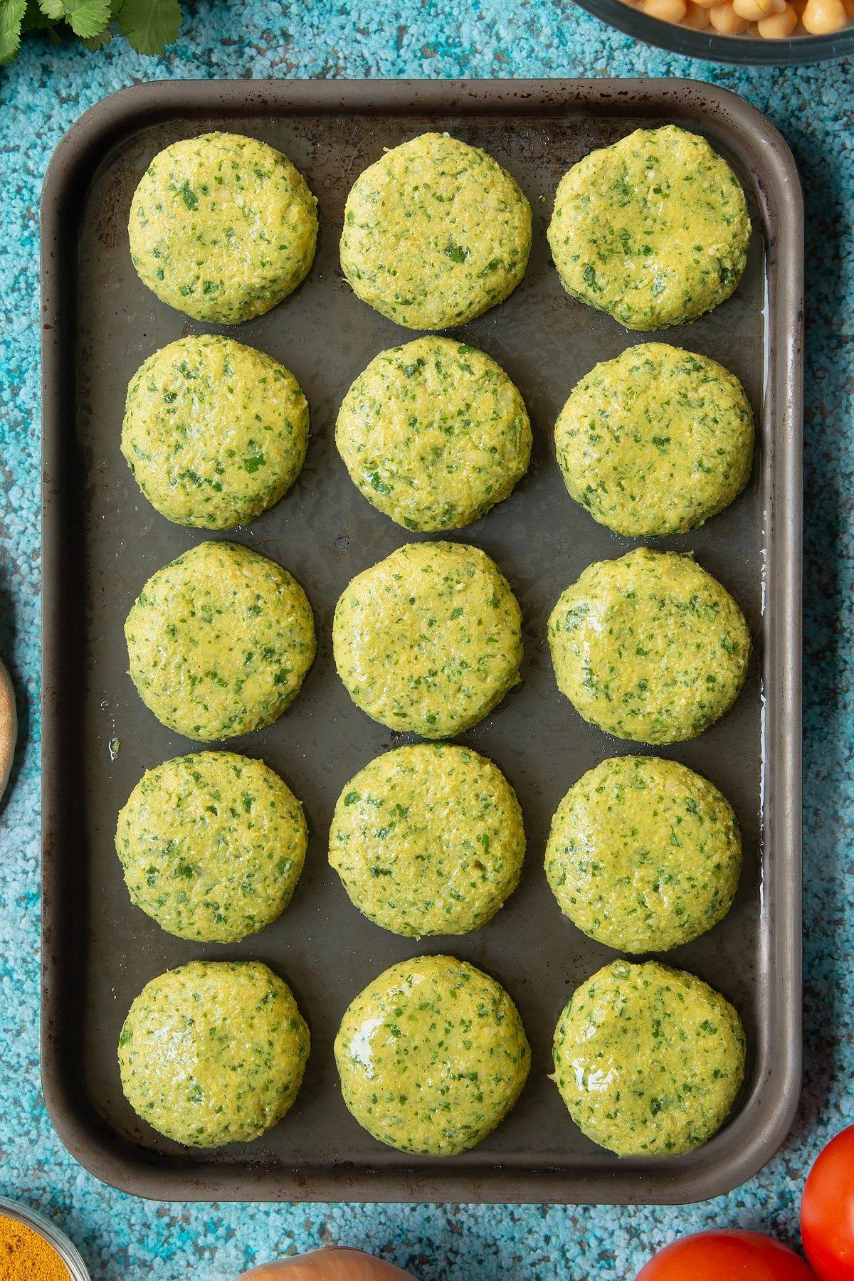 Oiled, raw gluten-free falafel on a baking tray.