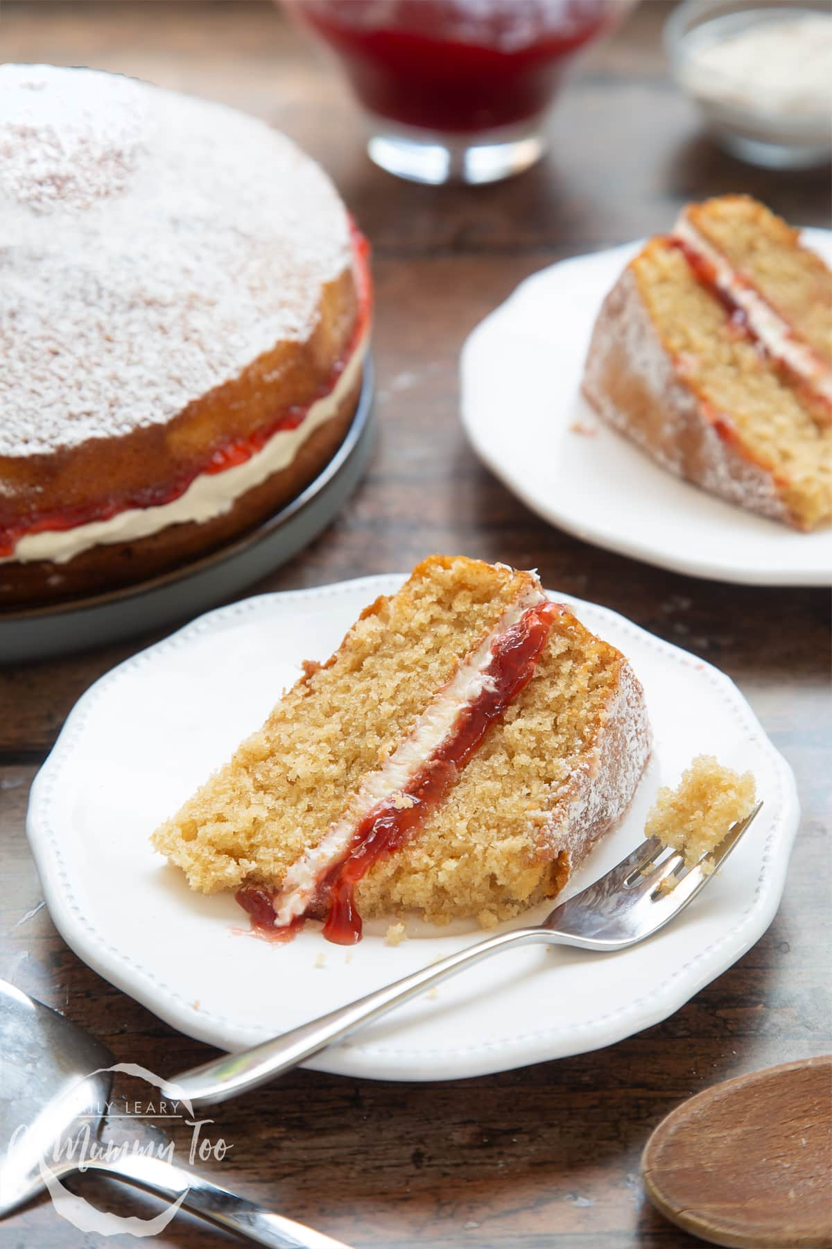 A slice of golden syrup sponge cake on a white decorate plate with a cake fork on the side. In the background there's an additional slice of cake as well as the cake as a whole.