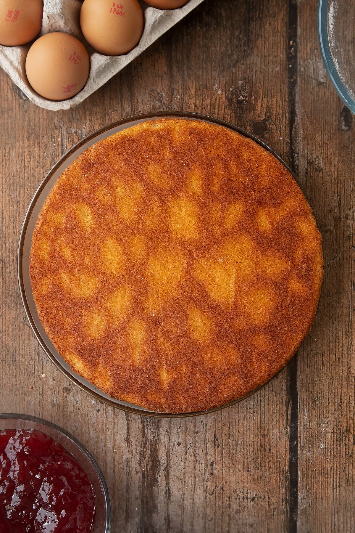 Overhead shot of Golden sponge cake on a wooden table.