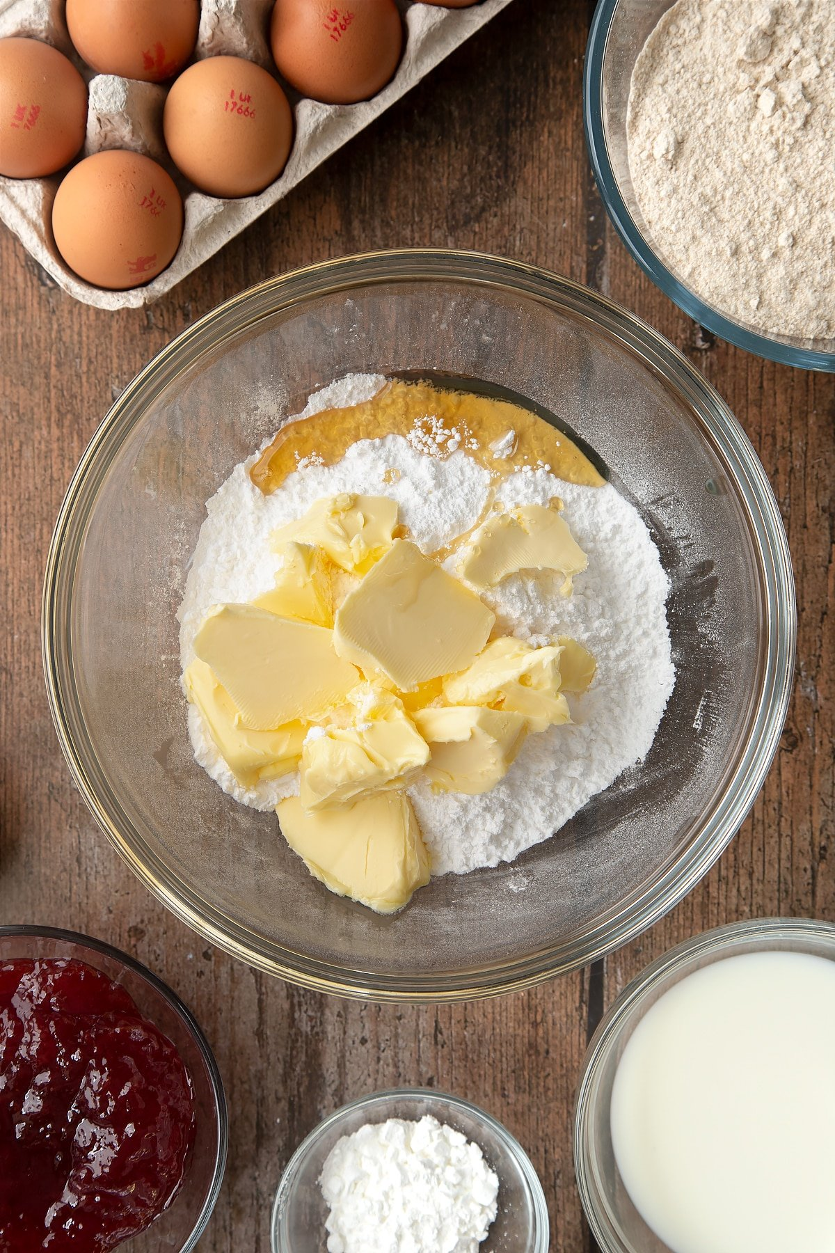 Overhead shot of sugar and butter in a large clear mixing bowl