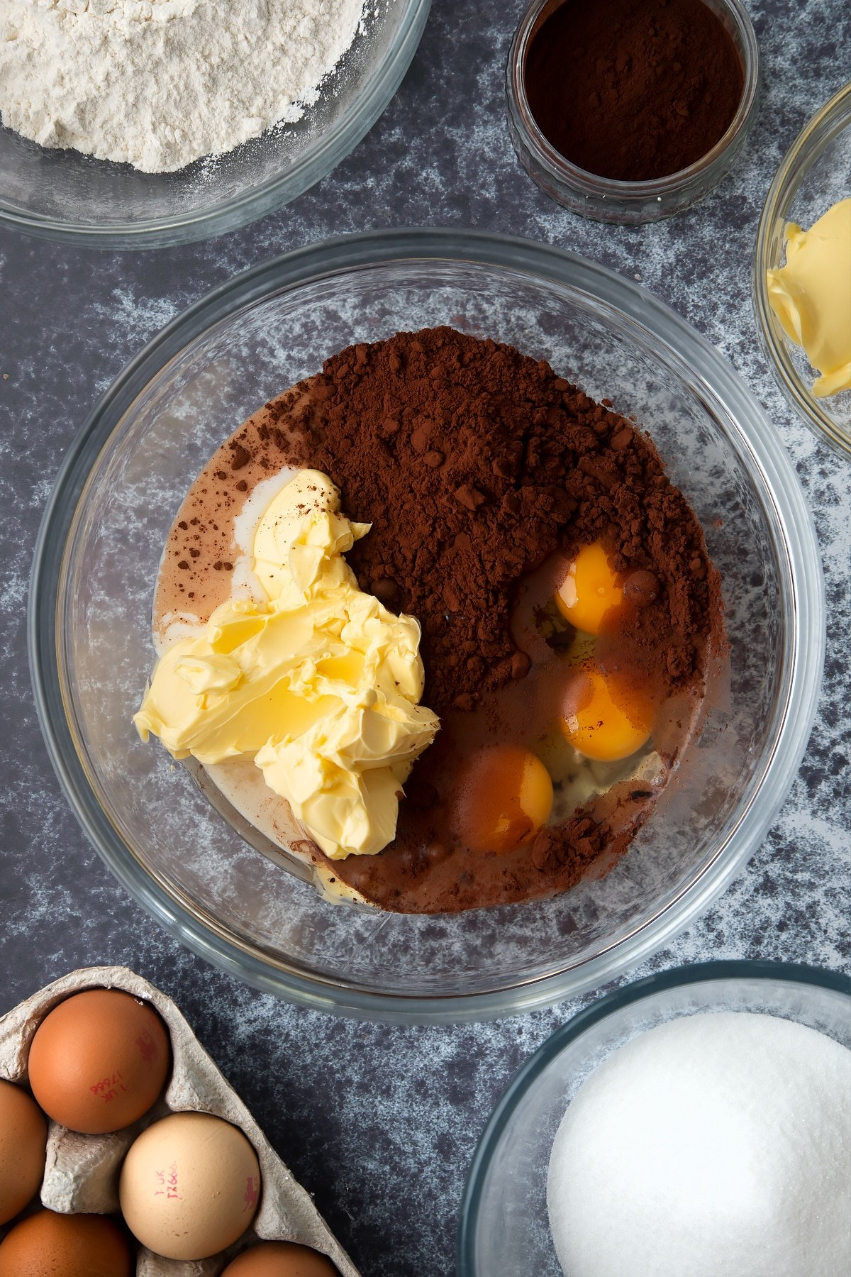 Margarine, oil, caster sugar, milk, cocoa and eggs in a large mixing bowl. Ingredients to make gory Halloween cupcakes surround the bowl.