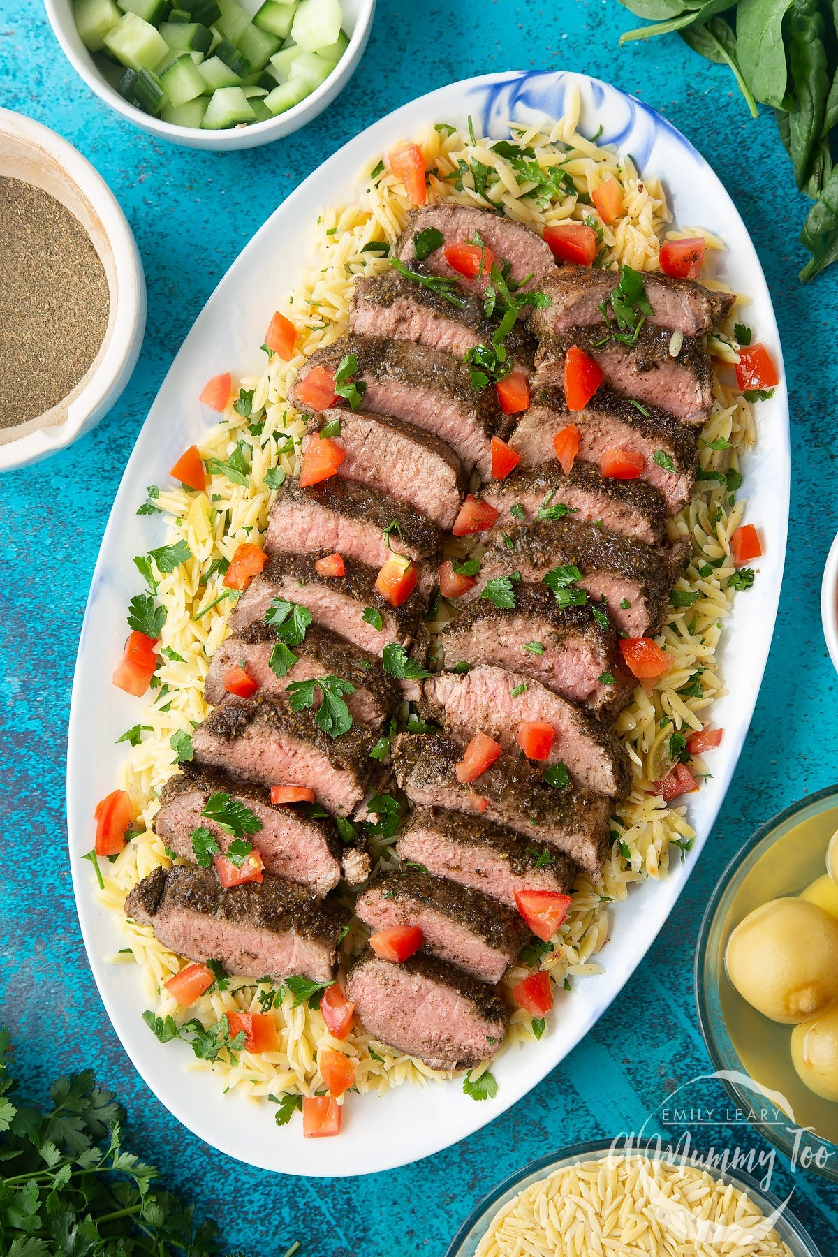 Slices of herby lamb arranged on a bed of orzo on an oval platter. The dish has been scattered with parsley and chopped tomatoes.