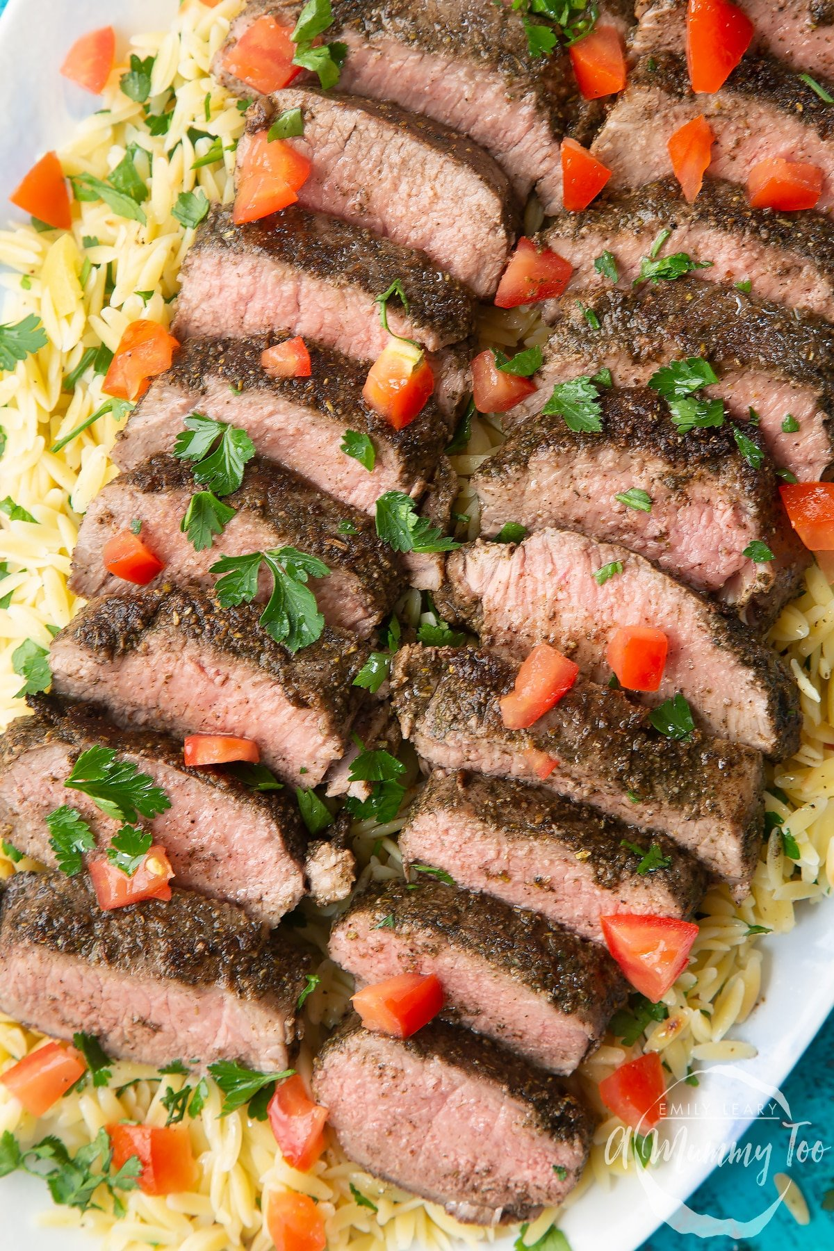 Close up of slices of herby lamb arranged on a bed of orzo on an oval platter. The dish has been scattered with parsley and chopped tomatoes.