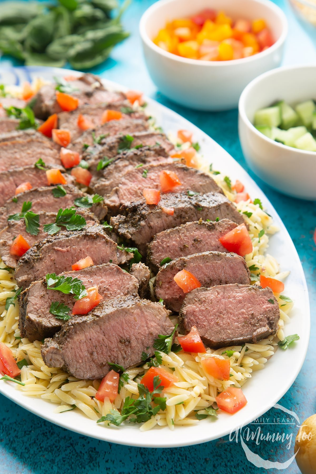 Slices of herby lamb arranged on a bed of orzo on an oval platter.