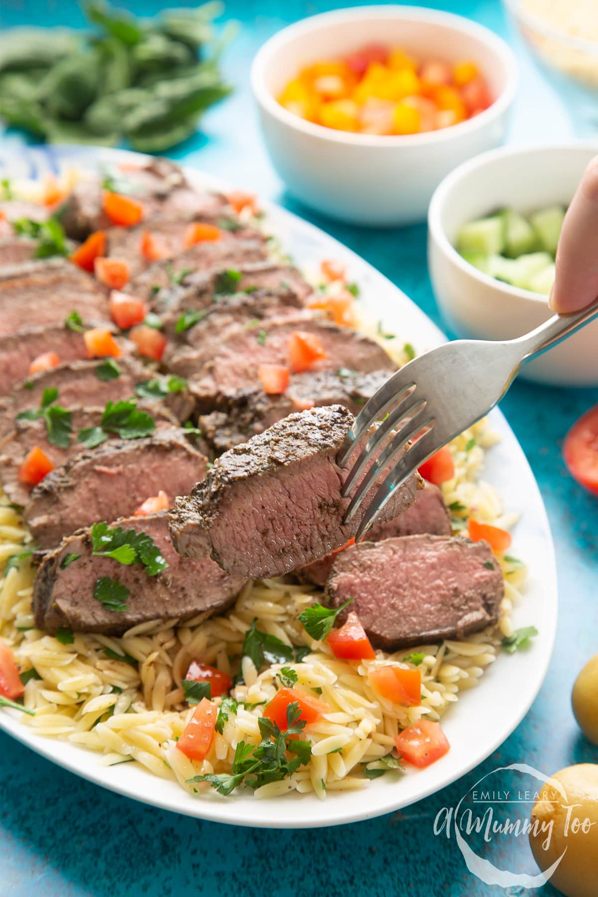 Slices of herby lamb arranged on a bed of orzo on an oval platter. The dish has been scattered with parsley and chopped tomatoes. A fork lifts a piece of lamb.