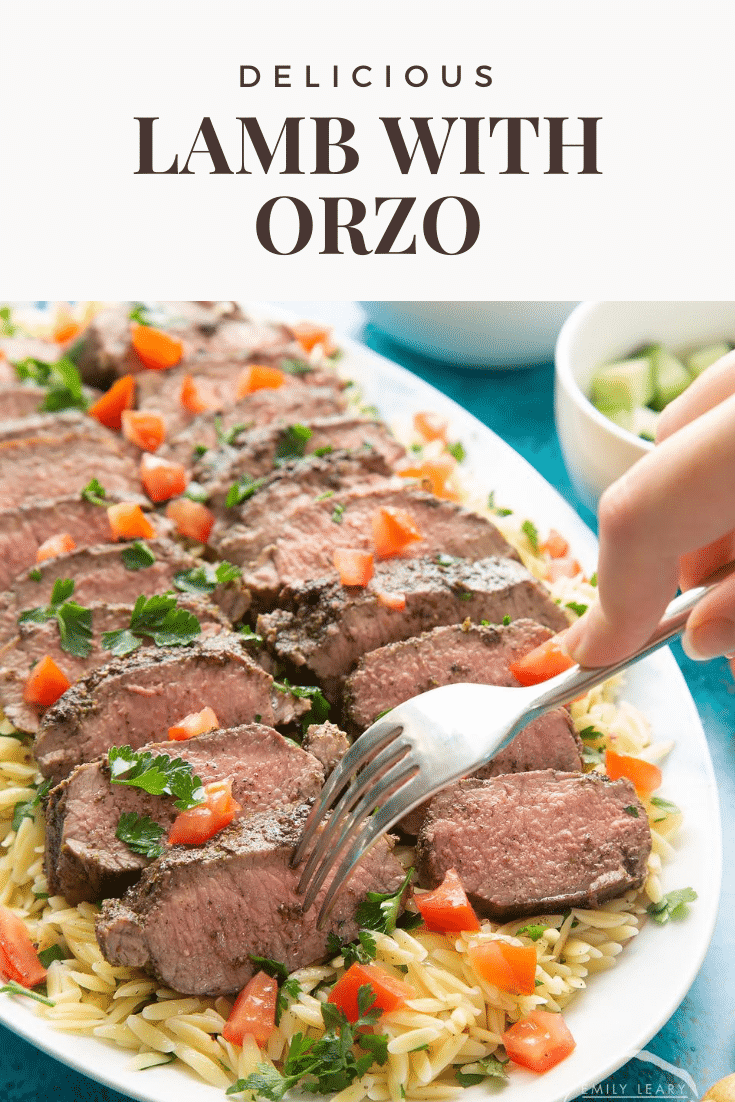 Slices of herby lamb arranged on a bed of orzo on an oval platter. A fork takes some lamb. Caption reads: delicious lamb with orzo