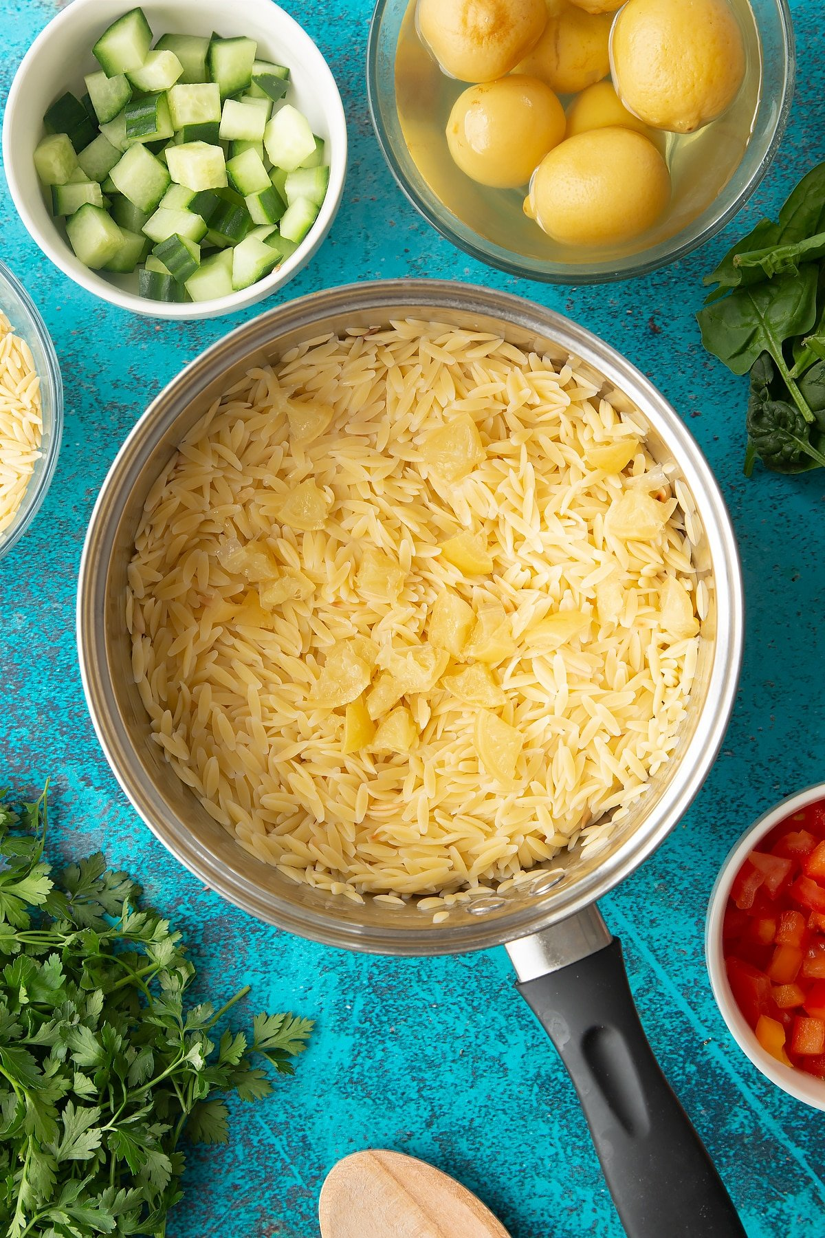Cooked orzo in a saucepan with preserved lemons on top.