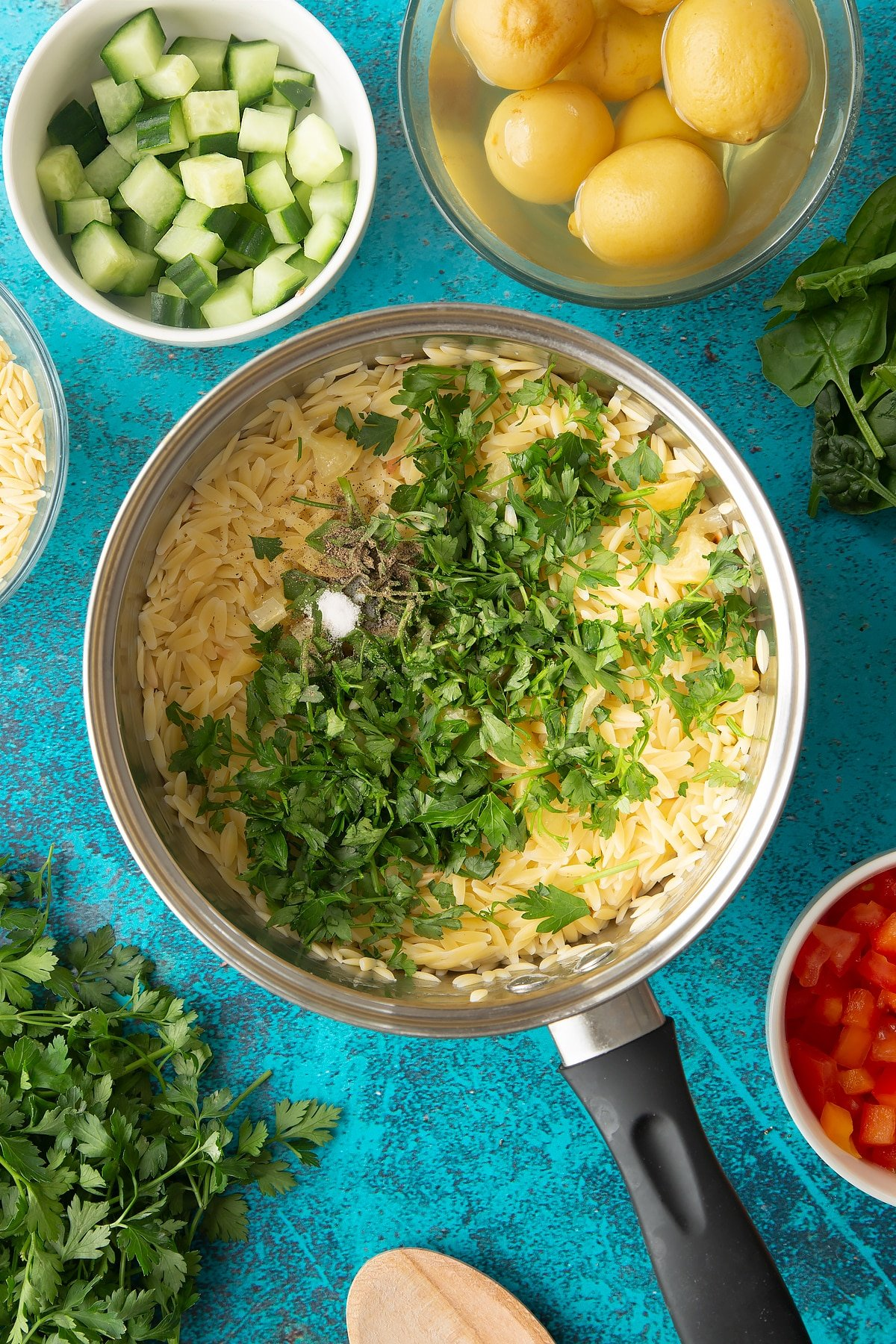 Cooked orzo in a saucepan with preserved lemons, parsley, salt and pepper on top.