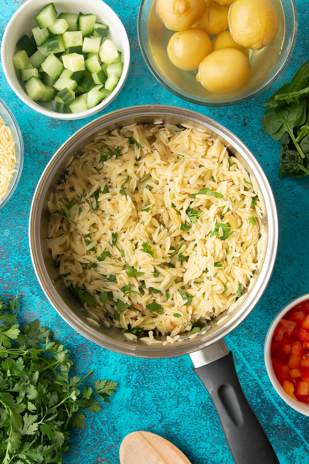 Cooked orzo in a saucepan mixed with preserved lemons, parsley, salt and pepper.