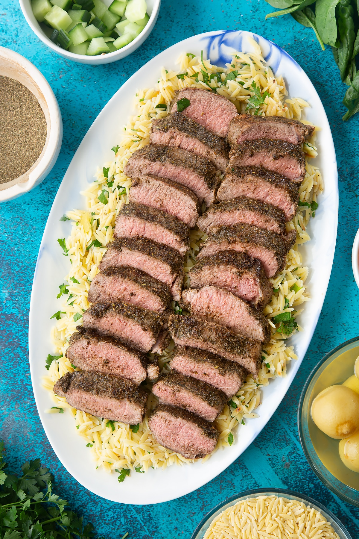 Lemony orzo spread on an oval platter, topped with slices of herby lamb.