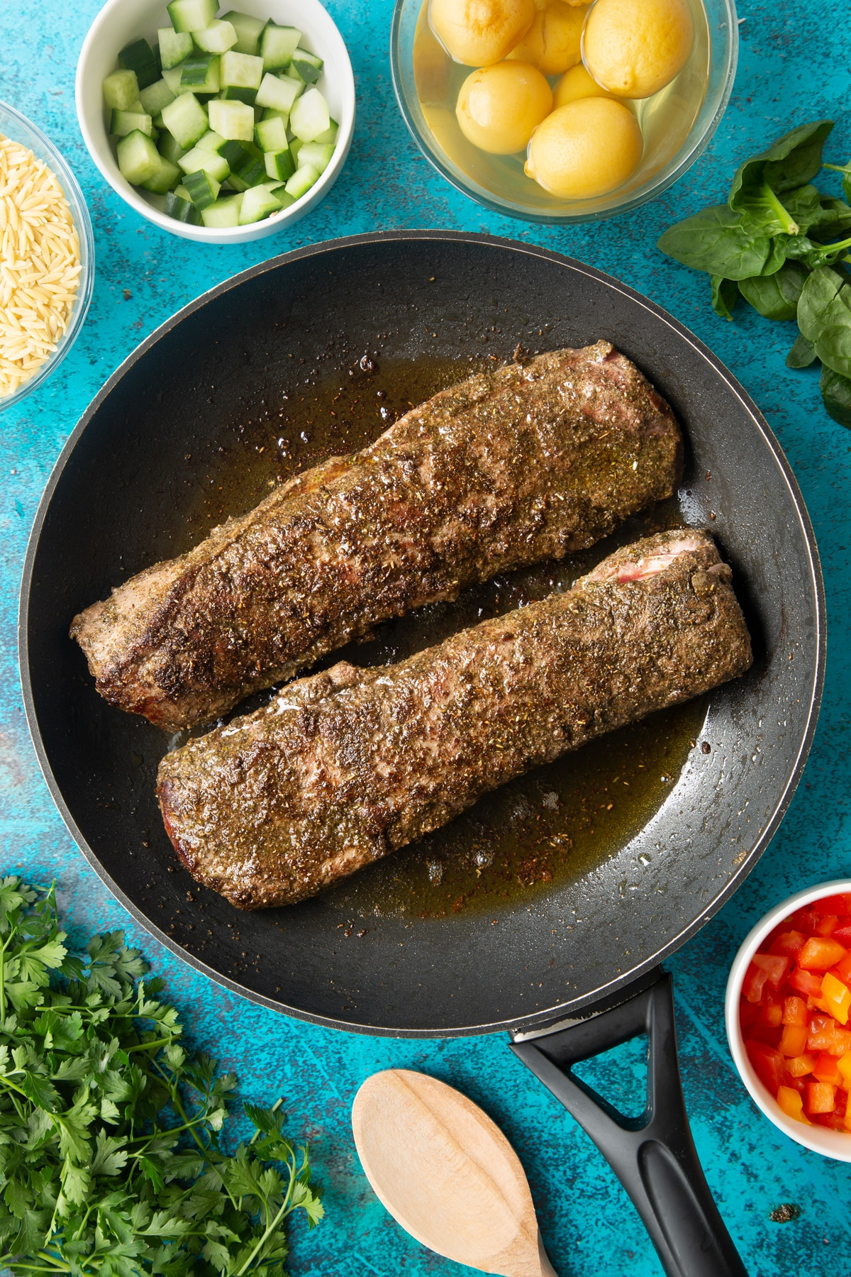 Two pieces of cooked cannon of Welsh lamb covered with a herb and oil rub in a frying pan.