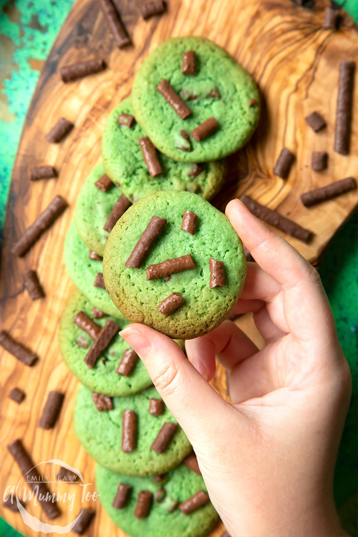 Hand holding a green cookie topped with Matchmaker pieces. More Matchmaker cookies are arranged on a wooden board below.
