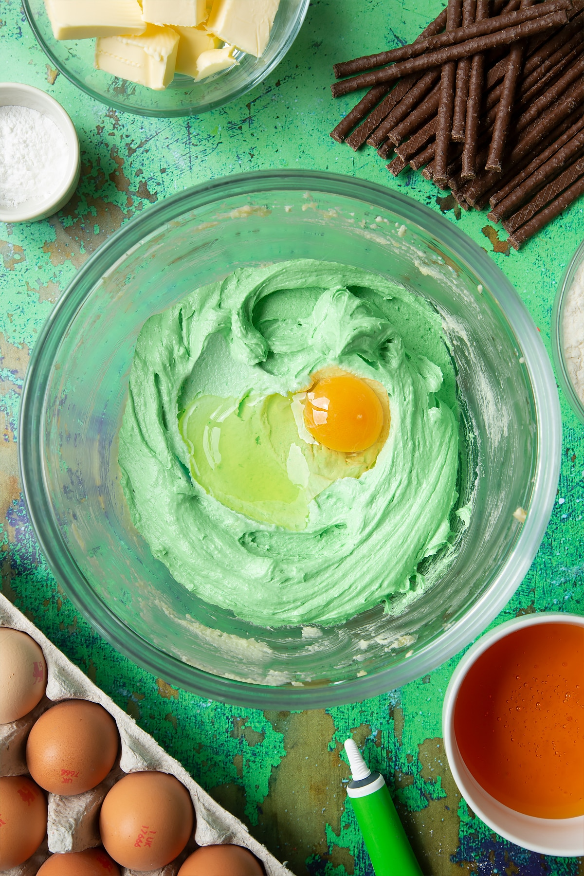 Creamed butter, sugar and green food colouring topped with an egg in a mixing bowl. Ingredients to make Matchmaker cookies surround the bowl.