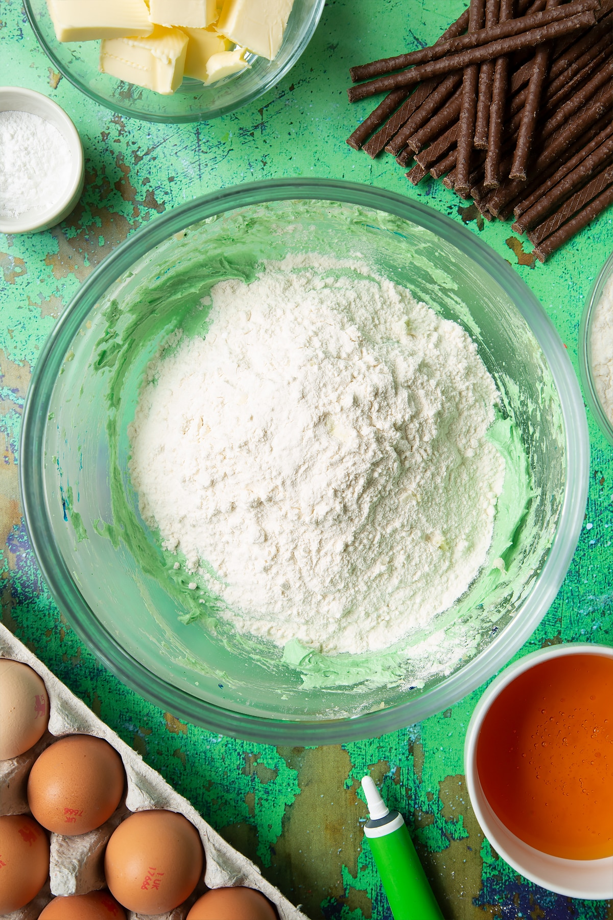 Creamed butter, sugar, eggs and green food colouring topped with flour in a mixing bowl. Ingredients to make Matchmaker cookies surround the bowl.