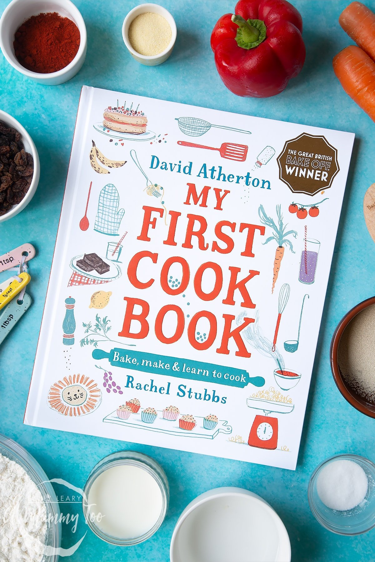David Atherton's My First Cook Book on a blue background surrounded by ingredients to make bread snakes.