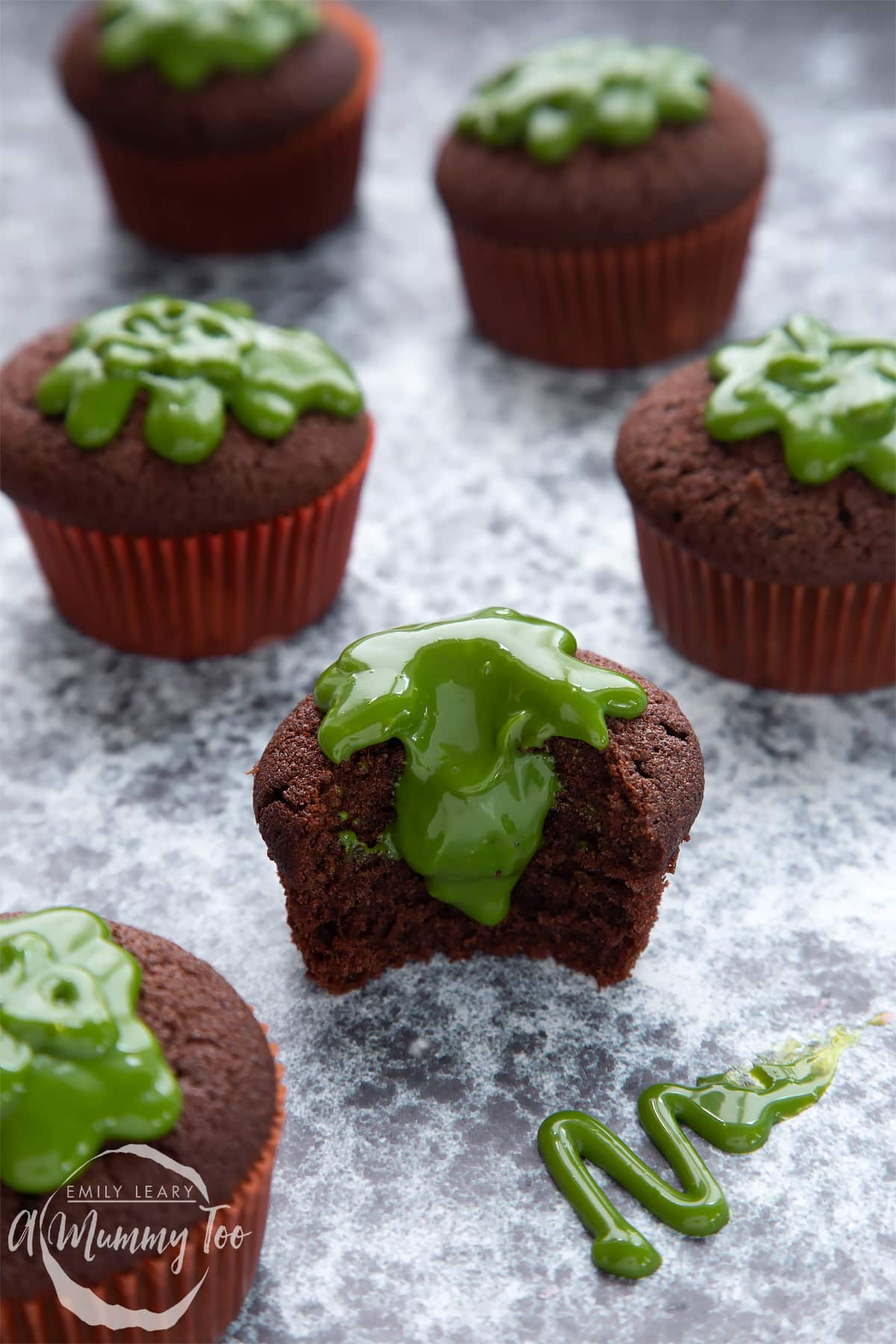Slime cupcakes on a black backdrop. The cakes have a chocolate sponge topped with dyed-green caramel. The cupcake in the foreground has been bitten into, revealing the caramel core.