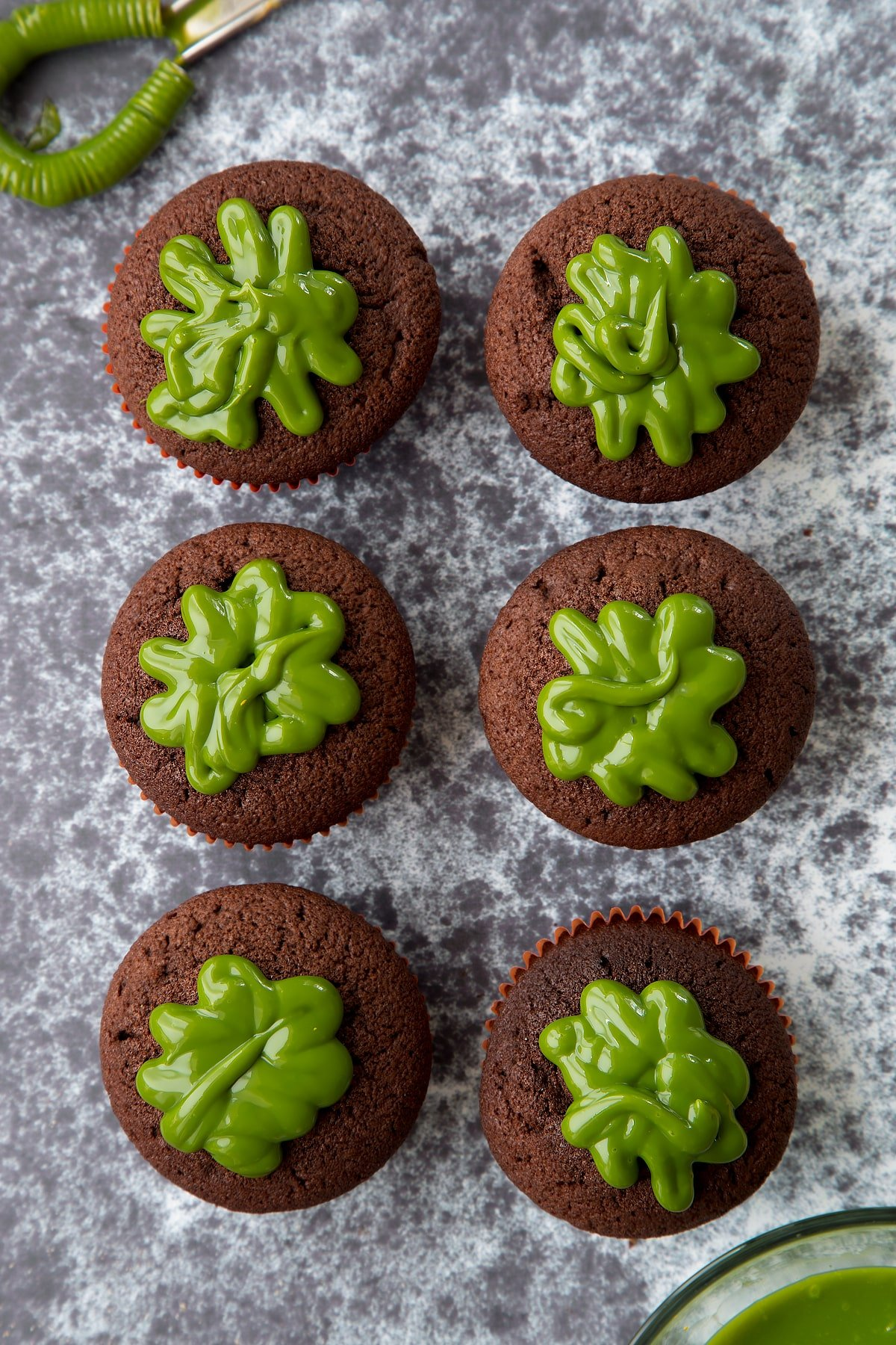 Six chocolate cupcakes shown from above. The cupcakes have been filled with dyed-green caramel.