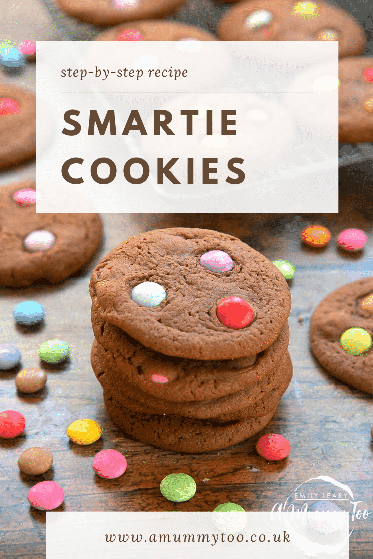 Smartie cookies stacked up on a dark wooden surface. Caption reads: step-by-step recipe Smartie cookies