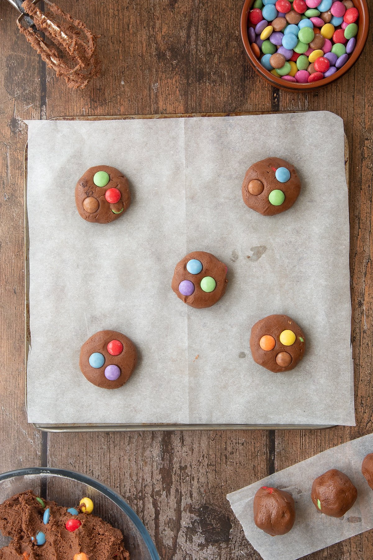 Smartie cookies on a baking tray lined with baking paper, ready to bake. Ingredients to make the Smartie cookie recipe surround the tray.