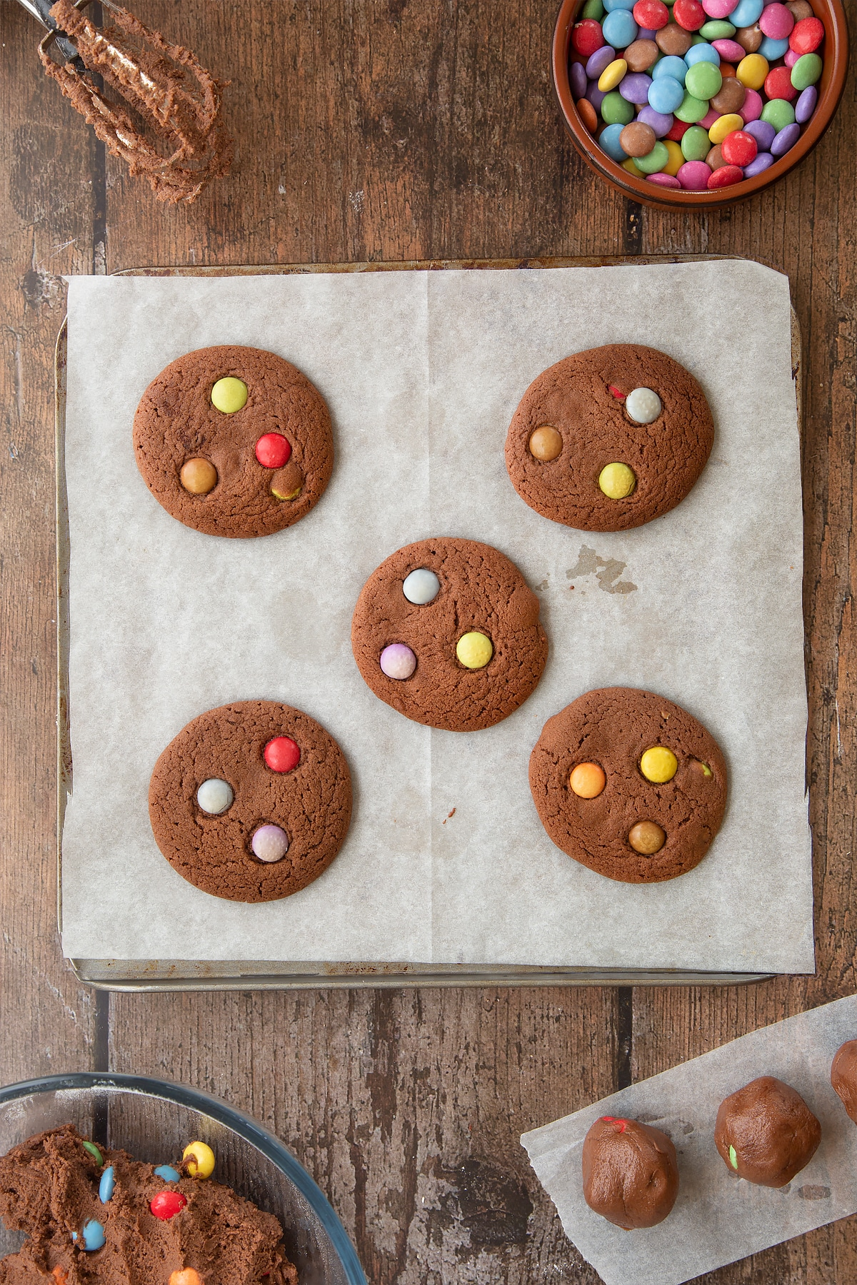 Freshly baked Smartie cookies on a baking tray lined with baking paper. Ingredients to make the Smartie cookie recipe surround the tray.
