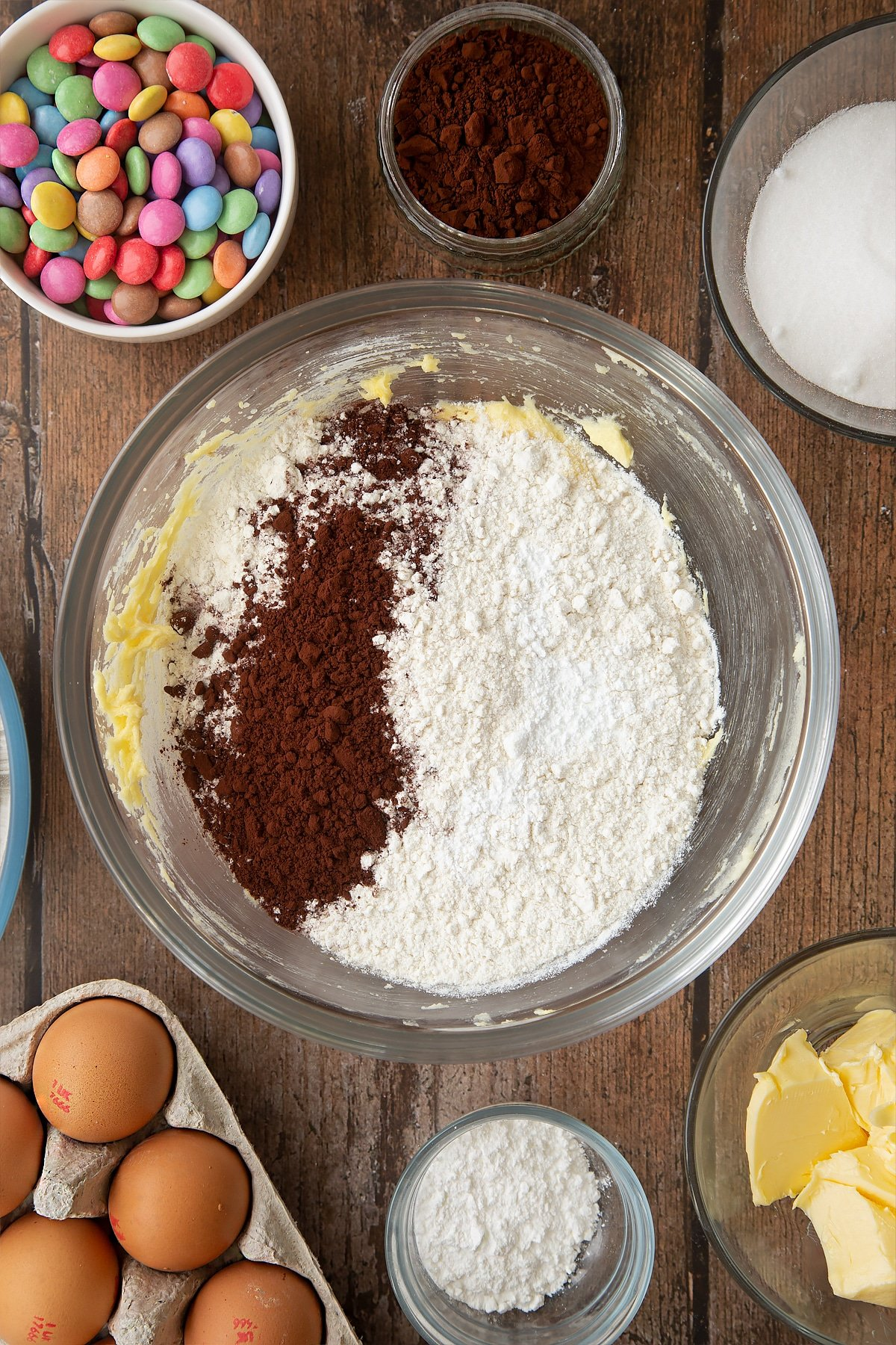 Beaten sugar, eggs and butter, topped with flour, cocoa and baking powder in a glass mixing bowl. Ingredients to make the Smartie cookie recipe surround the bowl.