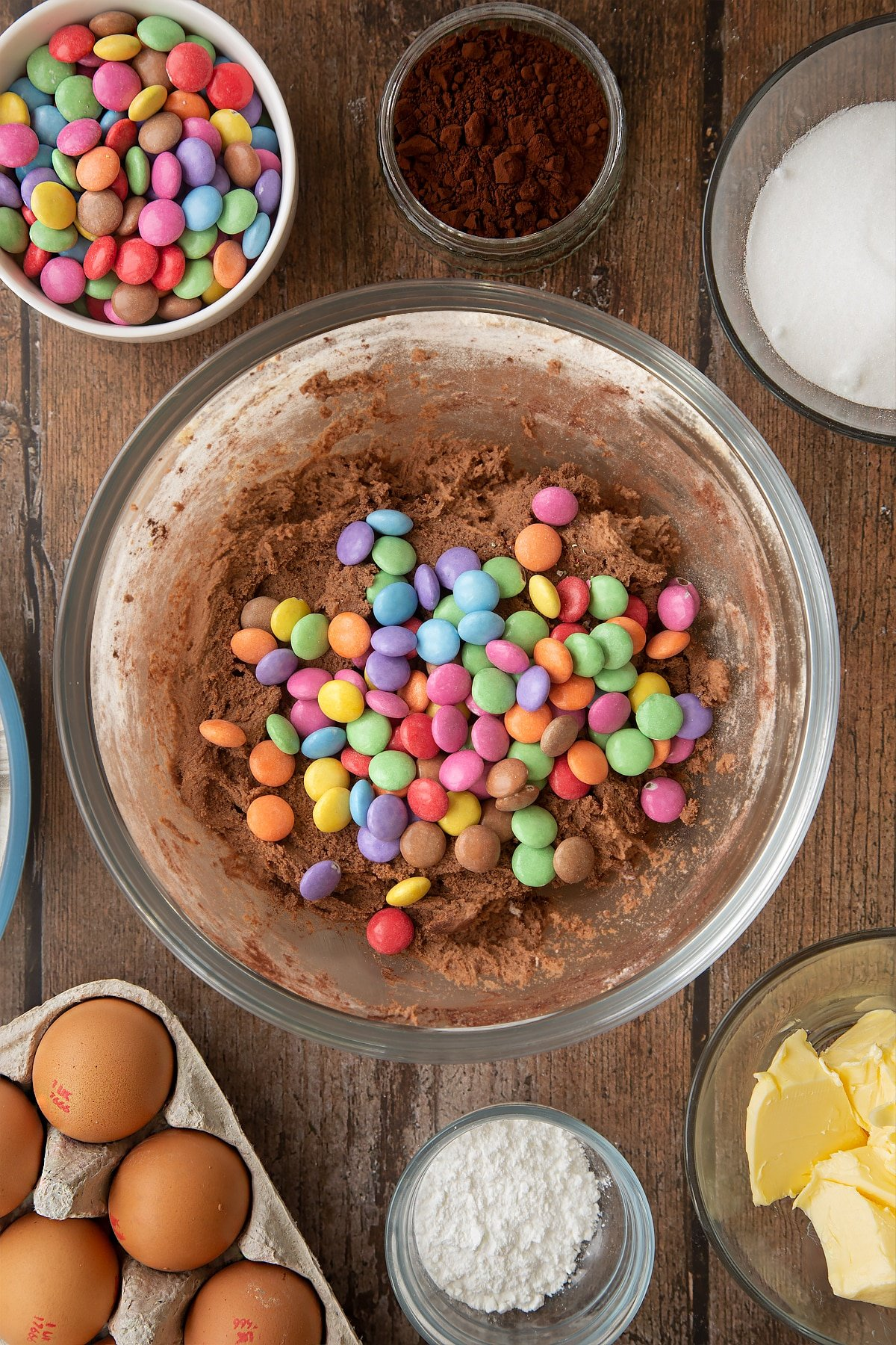 Chocolate cookie dough in a glass mixing bowl, topped with Smarties. Ingredients to make the Smartie cookie recipe surround the bowl.