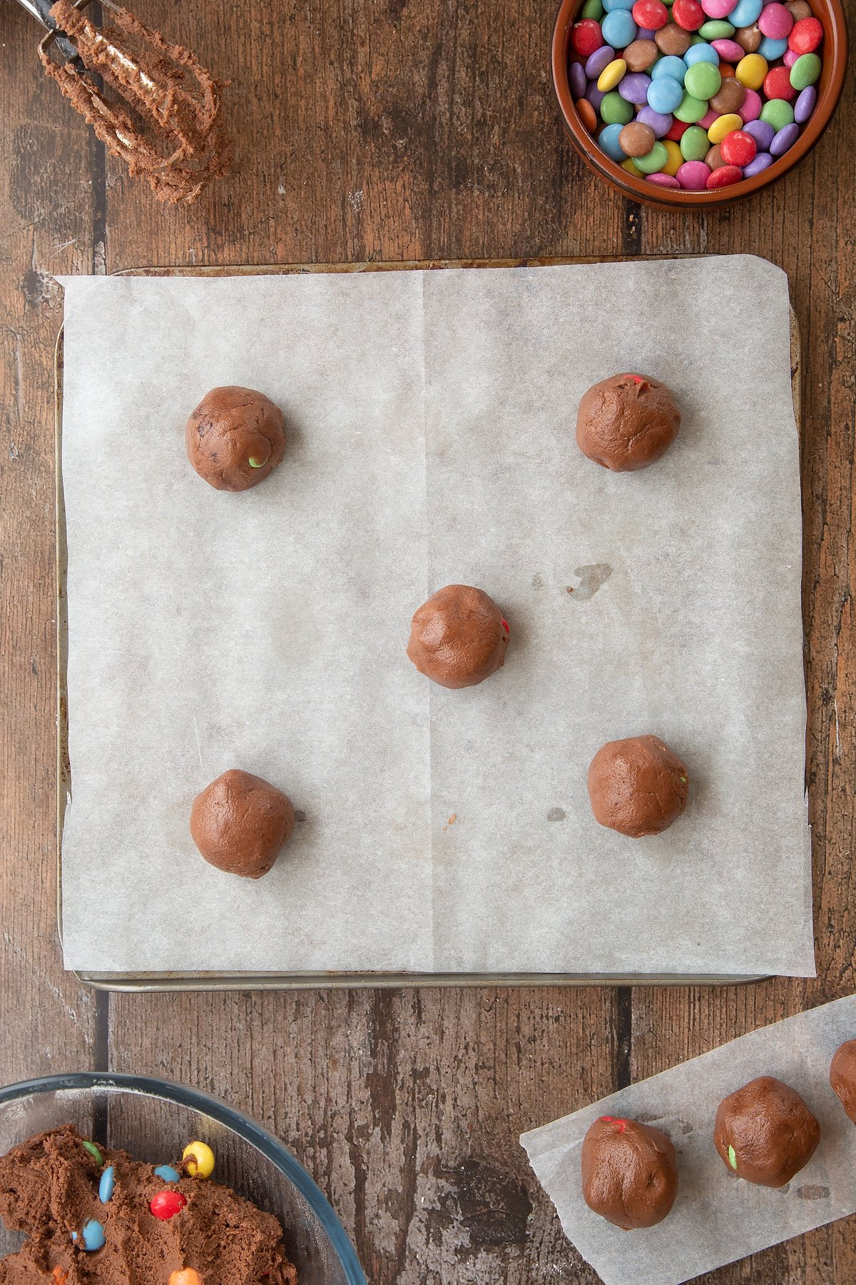 Balls of Smartie cookie dough on a  baking tray lined with baking paper. Ingredients to make the Smartie cookie recipe surround the tray.